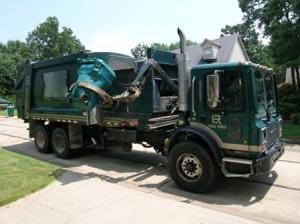Garbage Truck Picking Up Dumpster