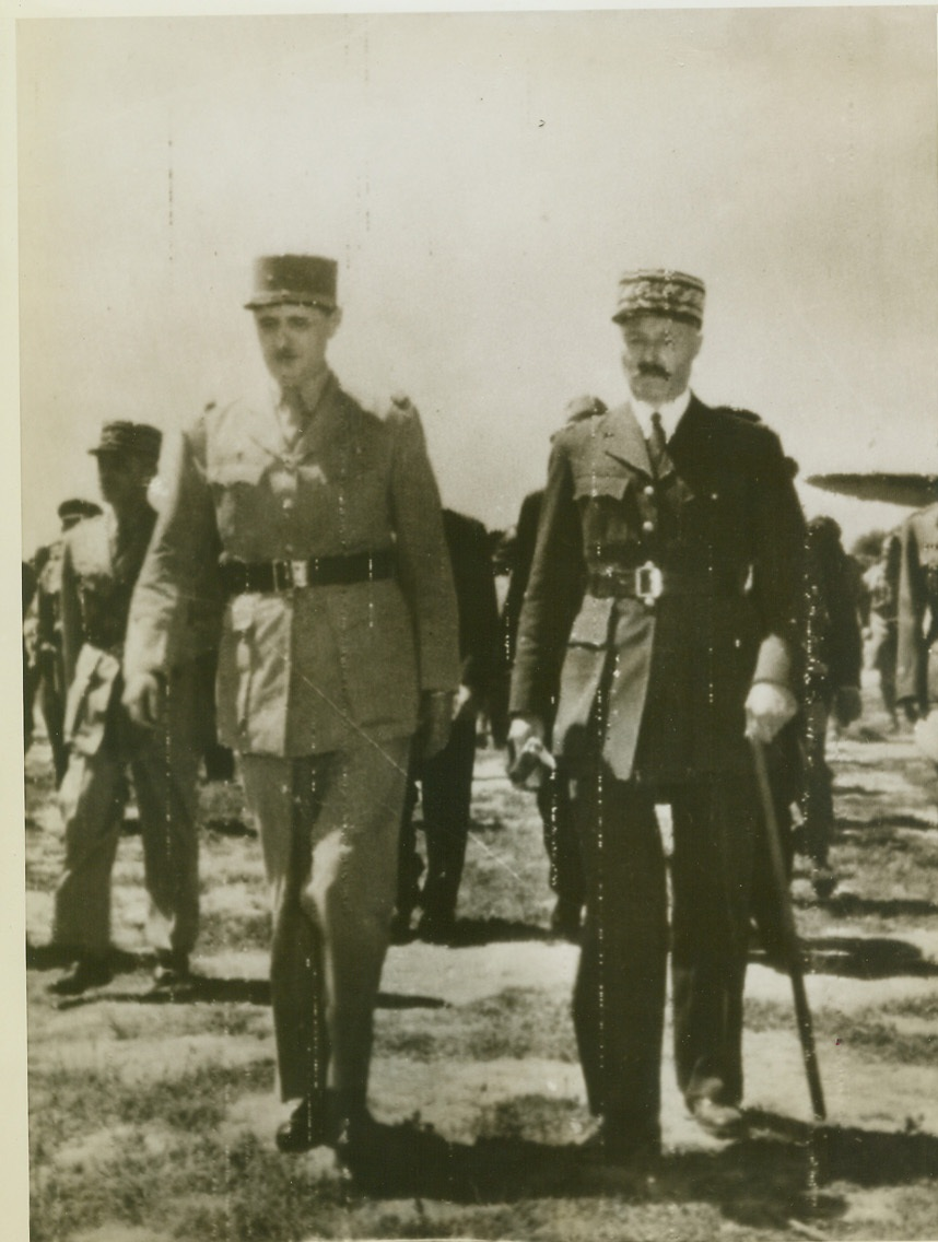 """HERALDING FRENCH UNITY, 5/31/1943. ALGIERS – After an exchange of salutes and handshakes, General Charles De Gaulle (left) and General Henri Giraud leave the airport outside of Algiers where the Fighting French General landed May 30 for the long expected meeting. A very select committee greeted De Gaulle –Vichyites excluded. Although no public announcement of De Gaulle's arrival was posted, the North African grapevine drew cheering crowds into the streets with cries of """"Vive De Gaulle."""" Credit: OWI Radiophoto from ACME;"""