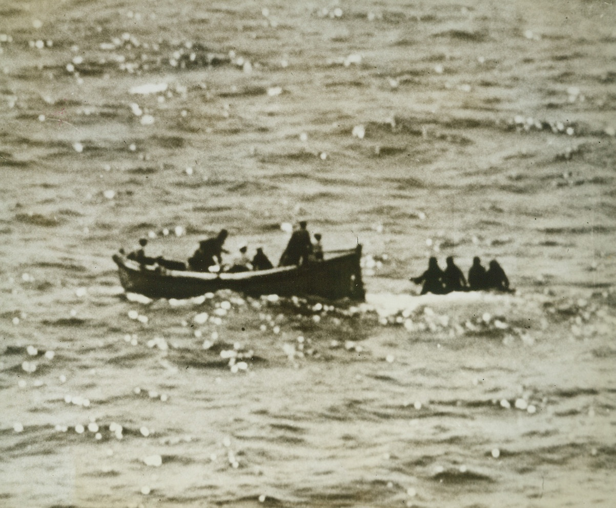 U.S.S. MARBLEHEAD RESCUES ARMY BOMBER CREW, 5/27/1943. Four members of an Army bomber crew who had been forced down at sea re picked up by a whaleboat from the U.S.S. Marblehead in a recent rescue by the famous Navy cruiser. The men spent five days on a rubber life raft in perilous seas without food and only eleven ounces of water.Credit: Off. U.S. Navy photo from Acme;