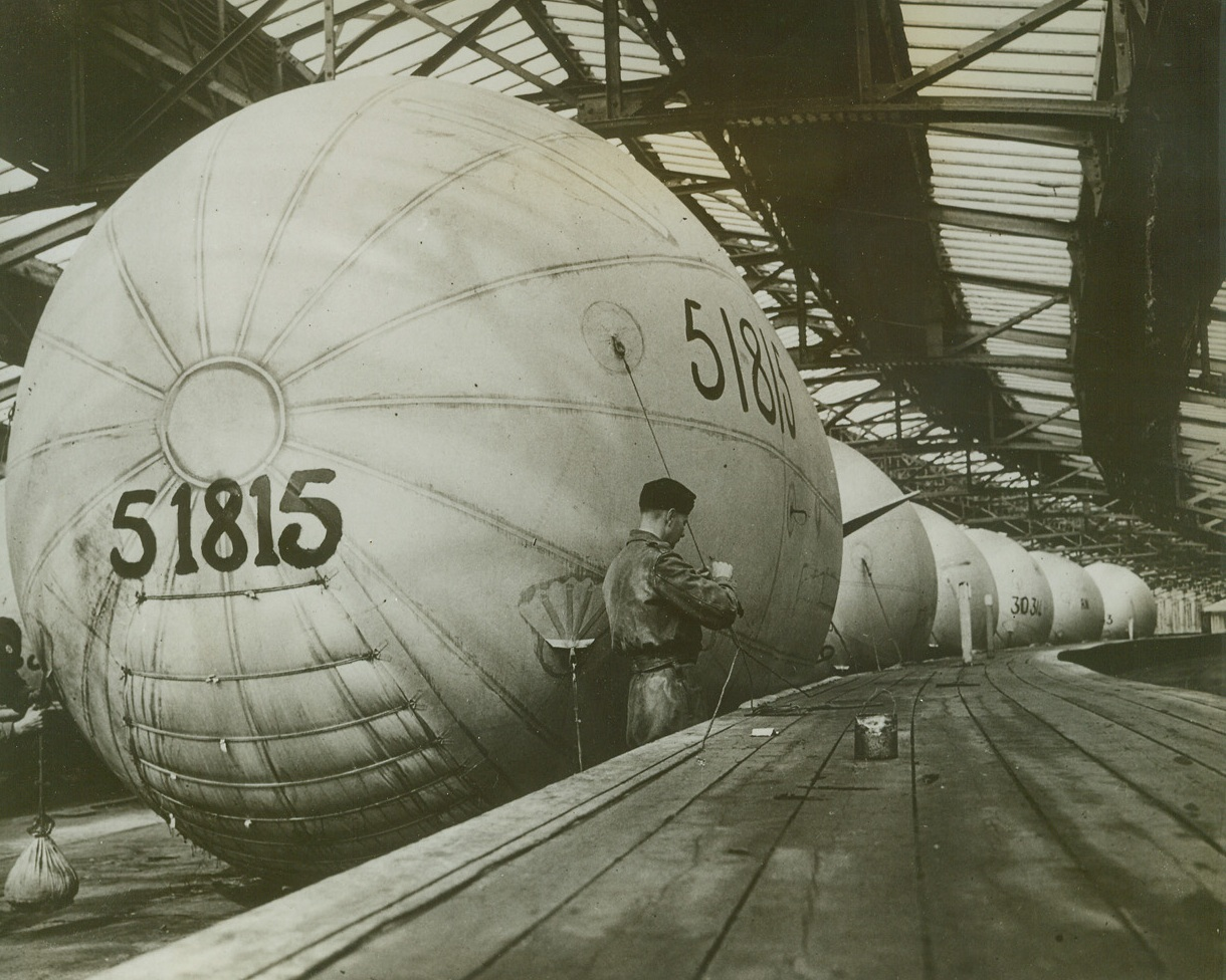 Inflation Line, 5/27/1943. SOMEWHERE IN ENGLAND—Mark VI balloons of the Royal Navy stand in line inside the inflation shed in which they are housed. Valuable because they help to protect ships from air attack, the balloons are used on drafters, trawlers, and other vessels.Credit: Acme;