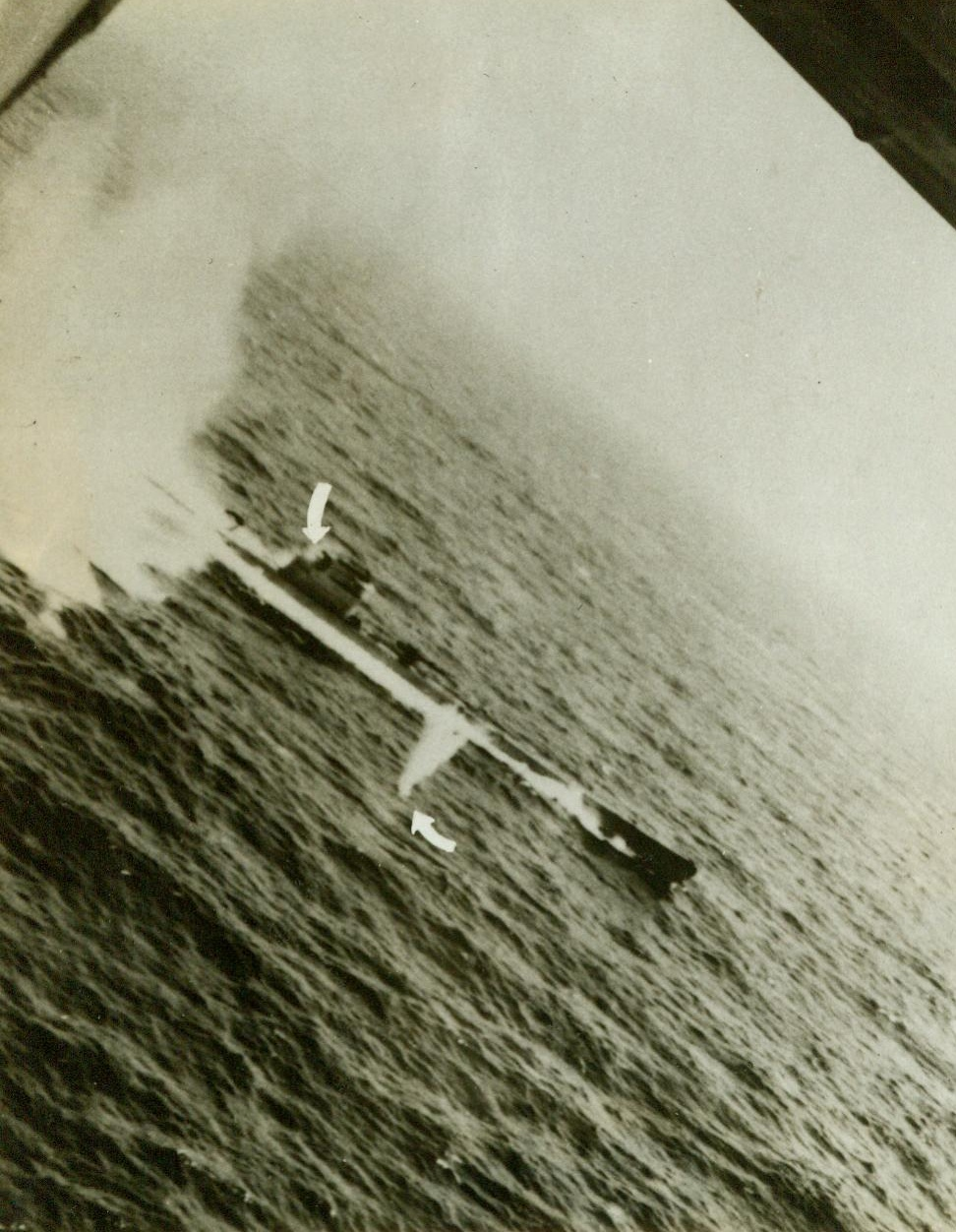 """""""Tidewater Tillie"""" Scores Again – (#1), 5/25/1943. The crew of a specially equipped Liberator B-24 Bomber of the U.S. Army Air Forces Anti-Submarine Command made this photo of a successful attack on a Nazi U-Boat, proving they had scored a """"kill"""". Once before they had attacked an enemy sub and had been given credit for only a """"Probable"""", because their photos hadn't shown conclusively that the undersea boat was destroyed. This time, photos of the attack, and of the wreckage on the surface after the attack made the """"kill"""" a certainty. Here, the B-24 comes in on its bomb run over the sub, its machine guns blazing. Arrow, (at left), shows a Nazi crew member hit and dropping to the deck, after an American bullet had scored a hit. Another machine gun bullet splashes into the sea, (arrow at right). A few seconds later, depth bombs from the plane blasted the sub to the bottom.  Credit line (U.S. Army Air Forces Photo);"""