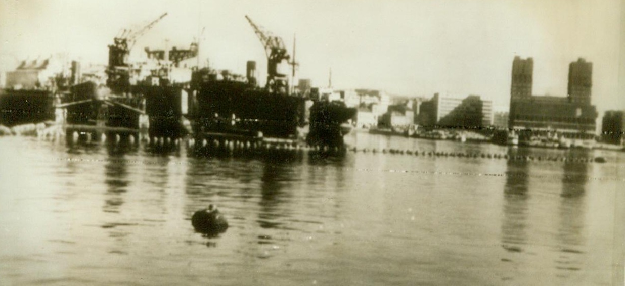INVASION NIGHTMARES, 5/27/1943. OSLO, NORWAY – Anti- torpedo nets protecting Oslo Harbor are mute testimony that the Nazis fear invasion in Northern Norway. In the background (left) is Akers Machine Factory, the country's biggest and (right) the Oslo City Hall, taken over by the Germans. Credit (ACME Radiophoto);