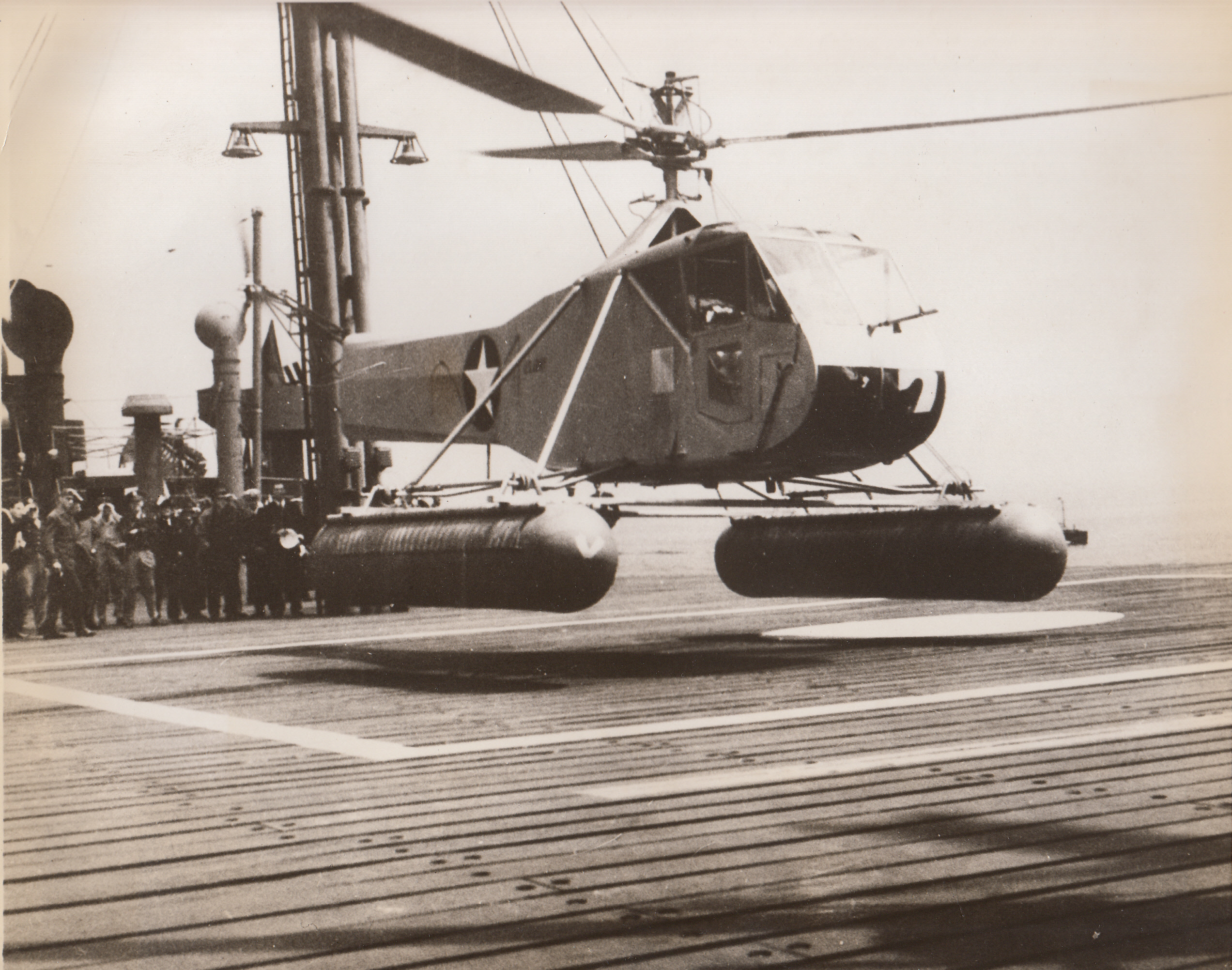 Helicopter Takes to the Ocean, 5/25/1943. A helicopter hovers over a small square marked off on the deck of a tanker, performing the tiny-space landing to prove its value as a sub fighter. In a recent demonstration on Long Island Sound, the wingless aircraft made 24 landings and take-offs from the small deck of a moving tanker. The craft, known as the Army Air Forces R-4 Helicopter, is an AAF development. A plan is in progress to install a small deck on Liberty ships to permit helicopters to be used at sea in anti-submarine duty.;
