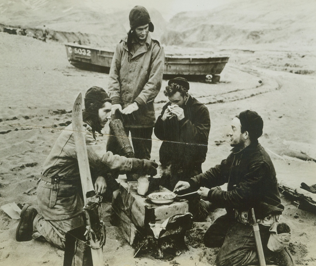 Double Purpose, 5/29/1943. Attu – A warm fire on Attu's chilly beach serves a double purpose.  It cooks a hot meal and thaws out the hands of these U.S. sailors in the Holtz Bay area of Attu island, following the landing there to drive out or destroy the Japanese Garrison.  Even in May that cold-weather garb and those skies (foreground) come in handy in the Aleutians.Credit (Official US Navy photo from ACME);