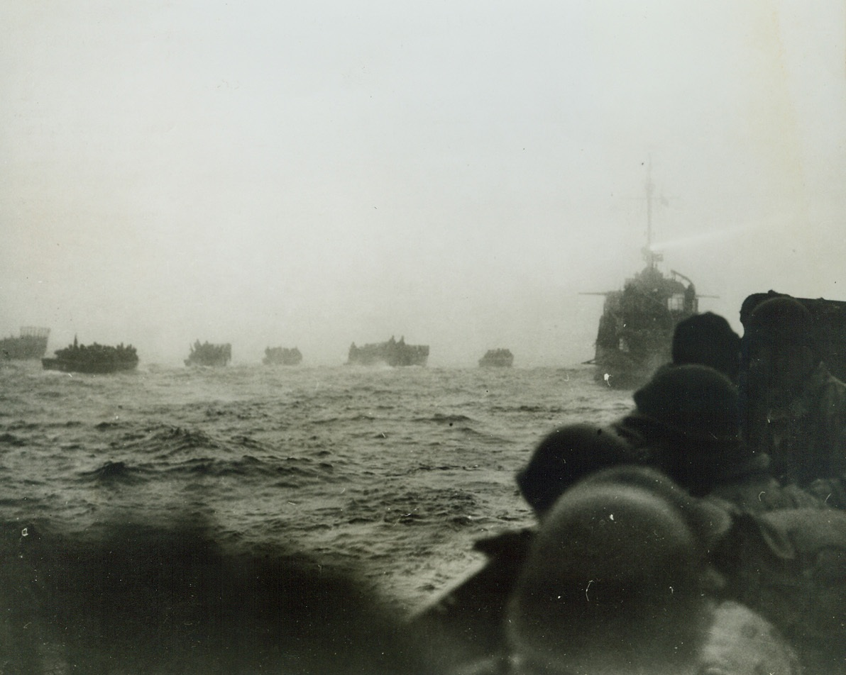 First Photos of Our Attack on Attu, 5/26/1943. As American troops landed on Attu, Aleutian islands, May 11, 1943, a Navy combat photography unit accompanied the first wave of American troops ashore at Japanese-occupied Attu, the Westernmost island of the Aleutian chain.  This photo was made at the start of the attack and shows that landing boats having been put over the side of the transports are beginning to move towards the beach.  The searchlight of the destroyer cuts thru the fog like a pencil.Credit Line (U.S. Navy official photo from ACME;