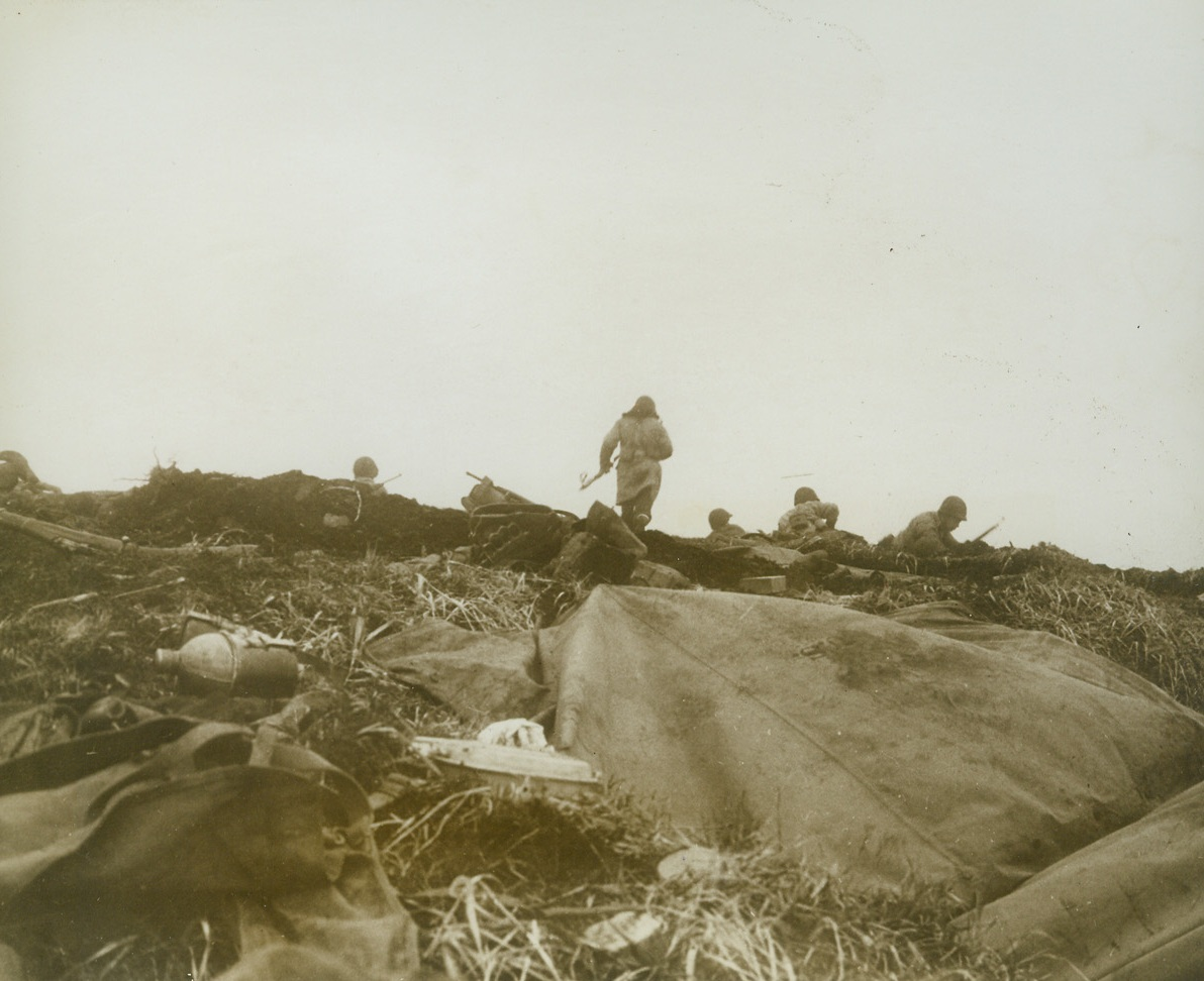 First Photos of Yank Landing on Attu, 5/26/1943. Washington, D.C.- - This photo, one of the first taken of the landing of U.S. troops on Jap-held island last May 11th, was taken by a Navy combat photographer and released in Washington today.  Cameramen who took these photos of the landing at two points on the island, Massacre Bay and Holtz Bay, were under Jap fire many times.  Here, U.S. troops advance in the face of enemy fire.  This is a front line shot made just as a bank of fog came rolling in.  While this photo was taken, Jap bullets were singing by.Credit Line (U.S. Navy photo from ACME);