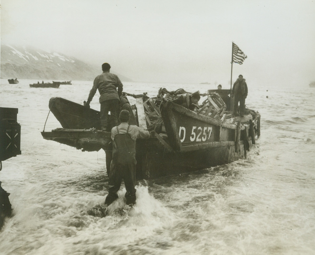 """""""Old Glory"""" Takes Possession,  5/27/1943. Attu – The American flag flutters from a mast in this captured Jap landing boat as our men bring it ashore on the beach of Attu's Massacre Bay.  Latest reports from that Aleutian Island indicate that fierce hand-to-hand fighting is now under way in the primitive wilds of Attu, with U.S. troops believed to be hacking their way through death traps with bayonet and grenade.Credit Line (Official U.S. Navy photo from ACME);"""