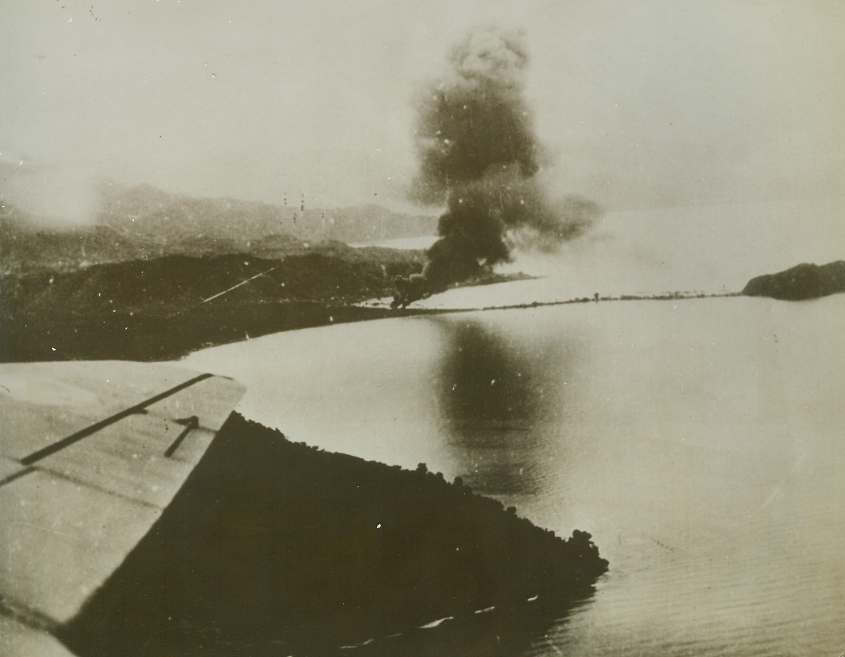 Allies Attack Salamaua, 5/20/1943. This photo, released in Washington today, shows smoke rising from fires set by Allied bombs on the Jap-held base at Salamaus, New Guinea, recently.  A wing of one of the bombers making the raid shows at lower, left (photo above).  It was announced today that allied planes had again raided Salamaua, attacking the airdome and town area and starting fires in enemy installations along the Francisco River.Credit Line (U.S. Army Air Forces photo from ACME);
