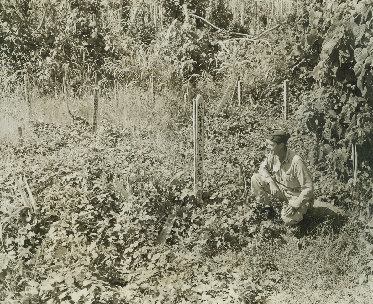 HERE LIES, 5/20/1943. NEW GUINEA—Deep in the heart of New Guinea's Sananada Jungle, slender tombstones jut out of the foliage to mark the resting place of Japs who fell in conflict with Allied forces. Tom Yarbrough, a War Correspondent, reads the inscription that marks the grave of Rotsune Yamamoto of the Jap Navy. Credit: ACME;