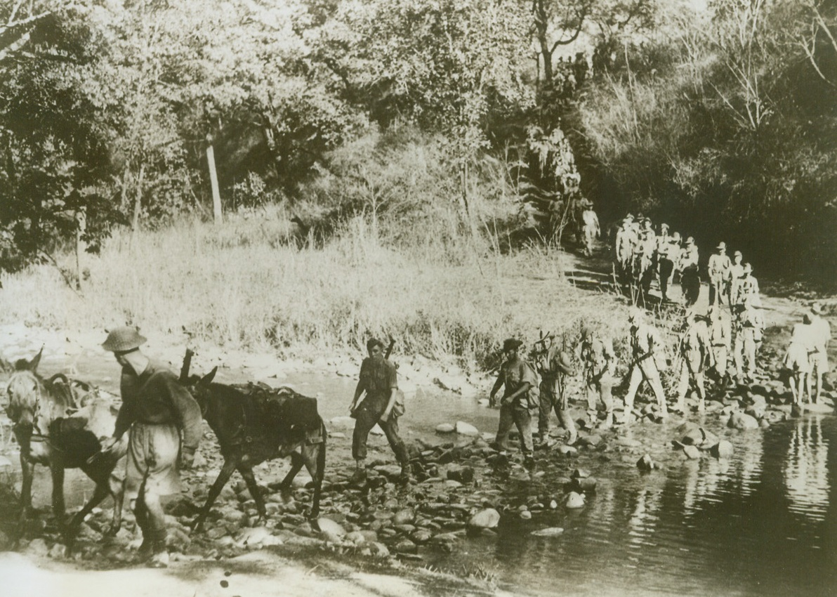 STEPPING STONES TO BURMA, 5/21/1943. BURMA—Stepping stones help Allied soldiers and their supply mules to cross this jungle stream on the narrow road to Burma. Cut through jungle, forests and mountains; this road must serve as a supply route for the Allies until the Japs can be chased from Burma and the Burma Road reopened. The key to China, which must be given military aid before a successful attack on the Japanese empire can be launched, Burma is probably the center of attention in long-range Pacific strategy discussions now being held in Washington.  Credit: ACME.;