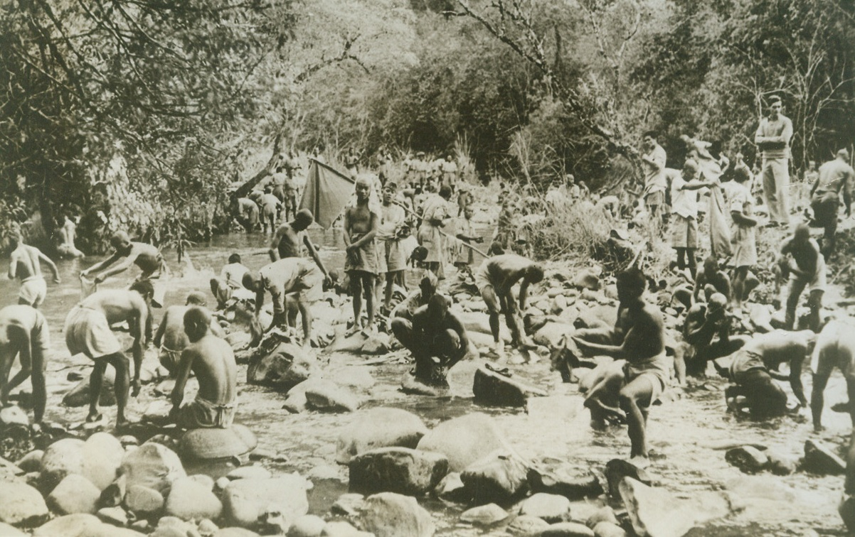 JUNGLE BATH, 5/21/1943. BURMA—Ubduab tribesmen wash the sweat of labor from their bodies and clothing in a rocky jungle stream along the new supply road to Burma. The tribesmen helped Allied troops to cut a supply route through miles of jungle, forests and mountains—which will have to serve the Allies until the Burma road can be reopened. Credit: ACME.;