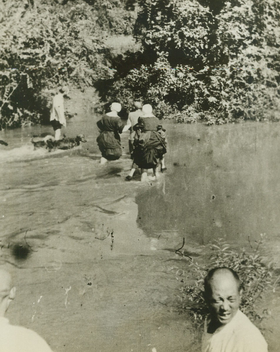 JAP SAVAGERY IN KIANGSI PROVINCE, 5/21/1943. From the camera of Vincentian priests, who served as missionaries in the Chinese Province of Kiangsi in October, 1942, when savage Jap troops visited the countryside to bring death and destruction to tiny towns that gave aid to General Jimmy Doolittle and his men, comes an eloquent record of the sufferings of the Chinese at the hands of brutal, vengeance-seeking Japan. Brought out of China by three priests and five American Sisters of Charity, who hid in the hills while the towns were laid waste, the pictures show violence that far surpasses damage done in modern bombing raids. The Chinese were tortured savagely and put to death en masse. Although the Japs had two objectives-the air field and 200 miles of railroad from Ying-tan to Chin-nua in Chekiang the general conduct of the rail was a punitive one, for it was here that American fliers were fed and treated after their raid of April 18, 1942. Fleeing China after the raid, the eight missionaries traveled on foot, by bus, and finally by boat and plane, reaching the Western Hemisphere five months later. The pictures were obtained in St. Louis from Father Paul Lloyd, director of the Vincentian Foreign Mission Society, and Father George Yager, the Vincentian priest who witnessed the raid and supplied captions for the following photos.  Holding their skirts high, American Sisters of Charity splash through a mountain stream as they flee the fast-approaching Jap Army of destruction. The Sisters abandoned their traditional headdress for the flight, to prevent the large, white headpieces from attracting the attention of aircraft.  Credit: ACME.;