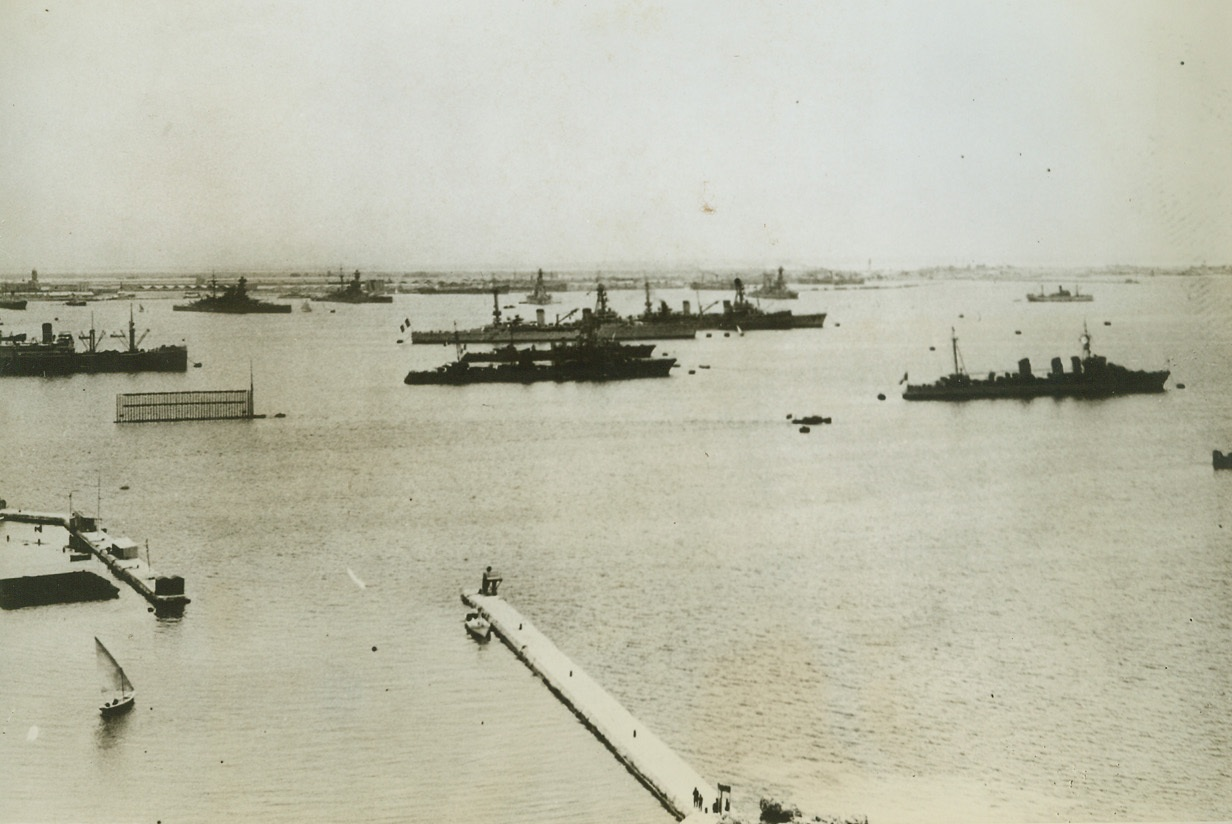"""French Egyptian Fleet to Come to New York, 5/31/1943. London – French warships at Alexandria (shown above), which have been lying immobilized since the Fall of France three years ago, have com under the allied control, according to a Berlin radio report last night.  The report, not immediately confirmed by any allied source, quoted a Vichy French Government announcement which said that the fleet """"had given in to American and British pressure"""" and that """"crewmen said they would join the allies.""""  One battleship, four cruisers, three destroyers, one submarine and a number of small auxiliary vessels make up the Alexandria fleet.Credit line (ACME);"""