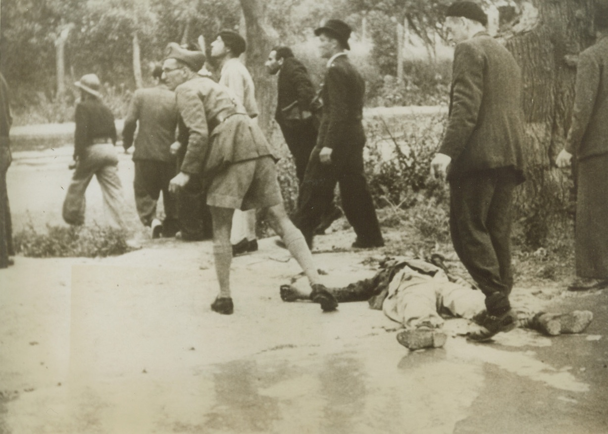 He Wouldn't Give Up, 5/19/1943. Tunis: - Soldiers and civilians took part in the street fighting that preceded the fall of Tunis.  On the ground is a dead Nazi – he wouldn't surrender.  He kept firing on British soldiers from a garden before meeting an untimely end. Credit line (ACME);