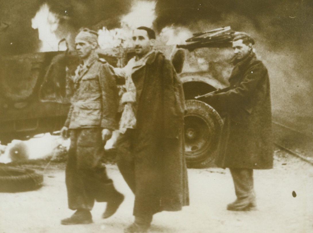 Allies Occupy Tunis, 5/19/1943. Tunis: - A British Tommy keeps his gun pointed at a pair of German prisoners whom he captured when Tunis fell to the allies.  The trio march past a Nazi vehicle that is still burning. Credit line (ACME);
