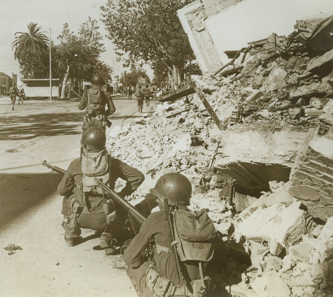 Yanks in Bizerte, 5/26/1943. Bizerte, Tunisia—Crouching beside the ruins of  buildings, a U.S. patrol awaits the order to move forward, while another patrol moves forward to reconnotter. Street to street and house to house fighting took place between Allied and Axis troops before Bizerte became Allied property.Credit: ACME.;