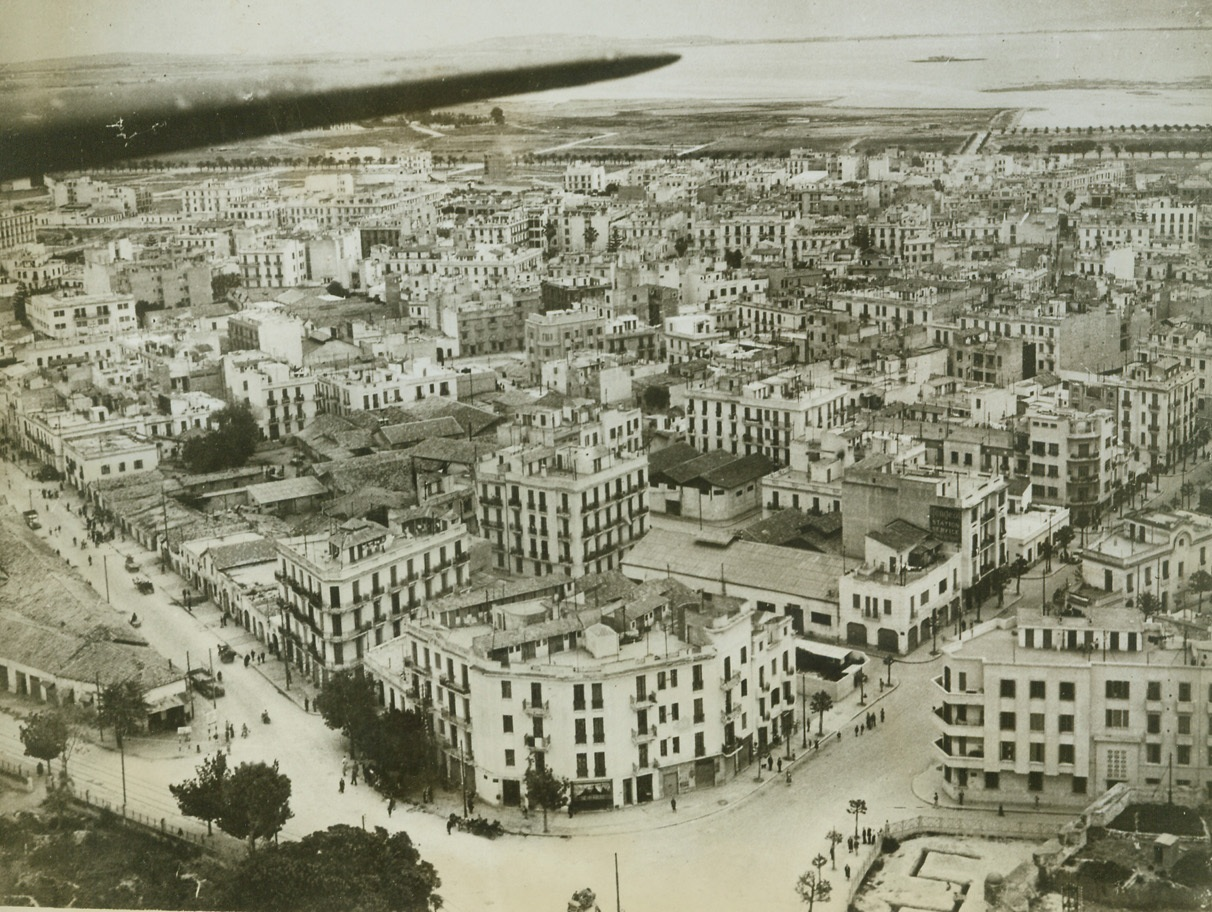 The City Still Stands, 5/22/1943. Tunis—Although Allied bombers pounded heavily at dock installations and military objectives in Tunis while the city was still held by the Axis, the center of the town was left almost intact. Untouched by bombs, this is how Tunis looked from the air soon after American, British, and French troops moved in. Only the trench at bottom right remains as a reminder of warfare that once raged in Tunis.Credit: ACME.;