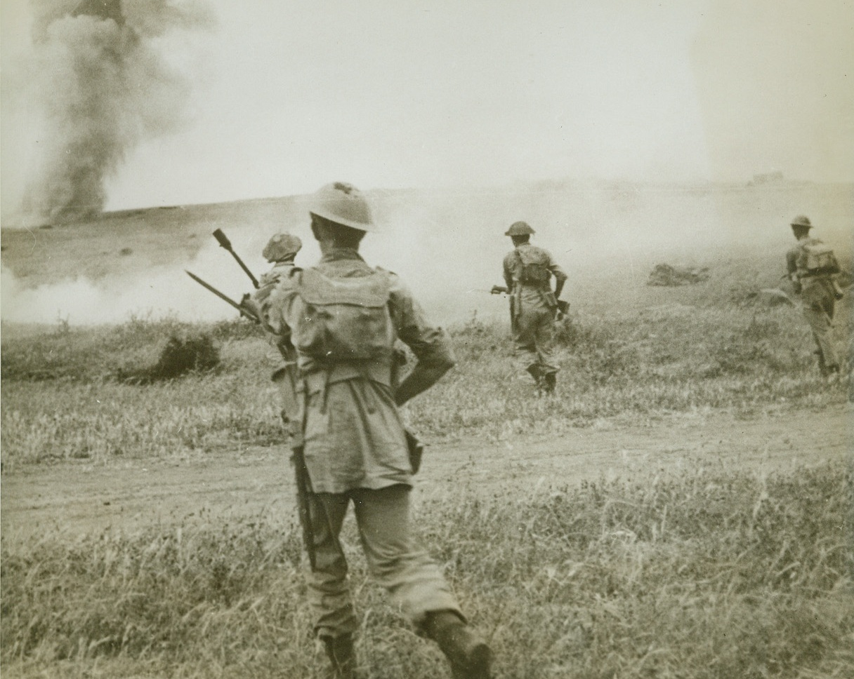 Smashing Through to Tunis, 5/24/1943. Tunisia, N. Africa—The day before the capitulation of Tunis, Eighth Army infantry rush a ridge while under fire from mortars and artillery. After fierce fighting, the British found the fall of the Tunisian capital unexpectedly swift. Credit: ACME.;