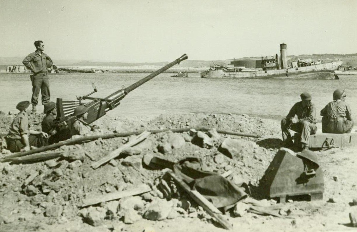On the Alert in Bizerte, 5/24/1943. BIZERTE, TUNISIA - As the Germans were...swept from Tunisia, the crew of a United...anti-aircraft gun maintain watch for...planes from a foxhole emplacement at...The hulk of a ship resting on bottom...harbor can be seen in the background...;