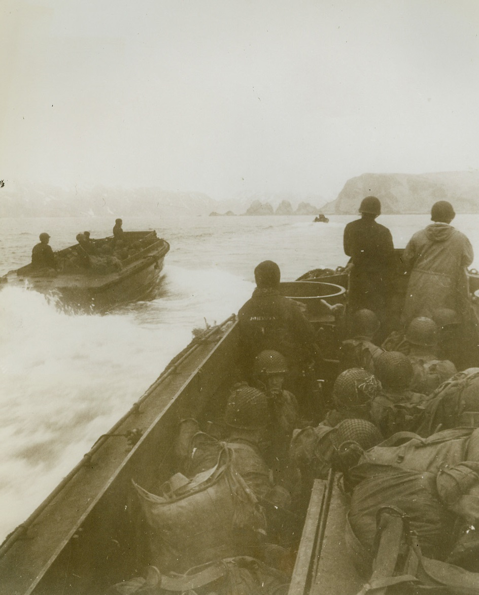First Photos of Yank Landing on Attu, 5/26/1943. Washington, D.C. -- This photo, one of the first taken of the landing of U.S. troops on Jap-held Attu Island last May 11, was taken by a Navy combat photographer and released in Washington today. Cameramen who took these photos of the landing at two points on the island, Massacre Bay and Holtz Bay, were under Jap fire many times. Here, heavily laden landing boats, with soldiers crouching down out of line of sniper fire, approach the west arm of Holtz Bay. Passed by censor. Credit: U.S. Navy photo from ACME;