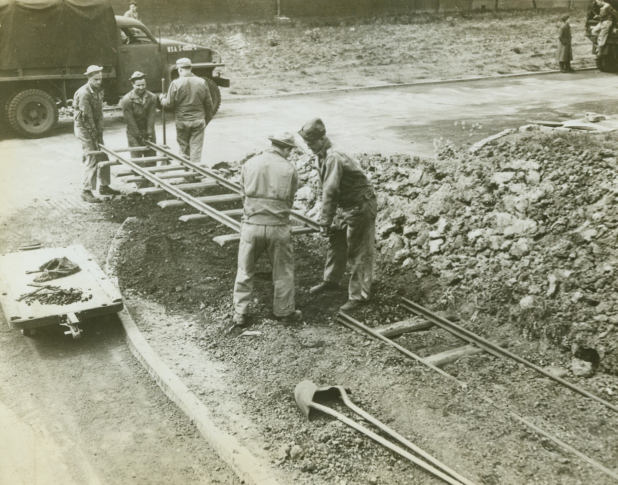 The Last Track, 5/22/1943. Somewhere in England -- American Army engineers lay the last bit of track for the 17-mile, narrow gauge railroad, built and operated by U.S. forces at an Army Supply Depot in England. The road was build to haul supplies between Army warehouses and unloading and shipping points in Britain. Credit: ACME;