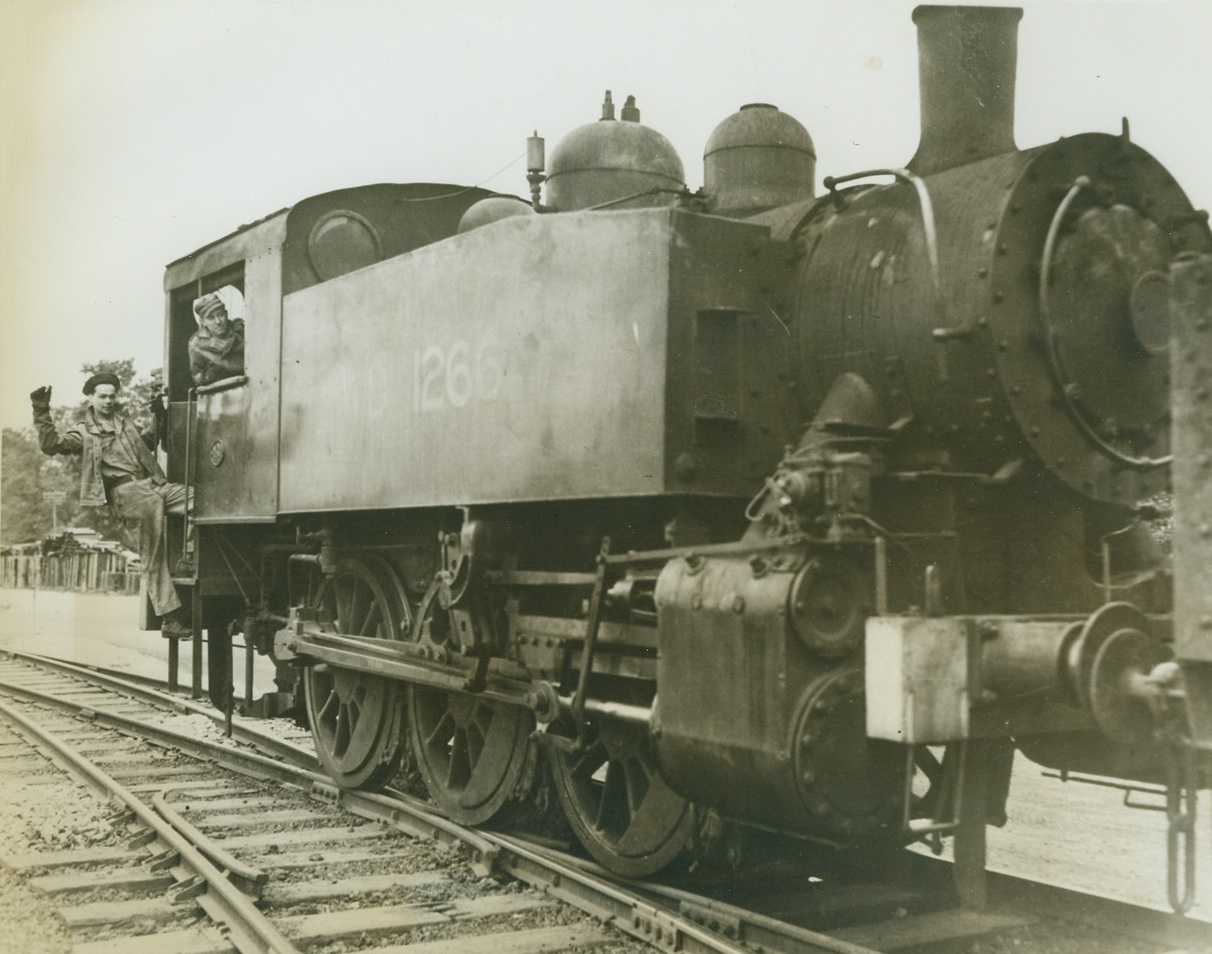 Rolling Along, 5/22/1943. Somewhere in England -- Rolling along the only American-built-and-operated railroad in England, this engine hauls Army supplies to and from Army warehouses. The 17-mile, narrow gauge railroad was built by U.S. Army engineers to facilitate transportation of equipment. Credit: ACME;