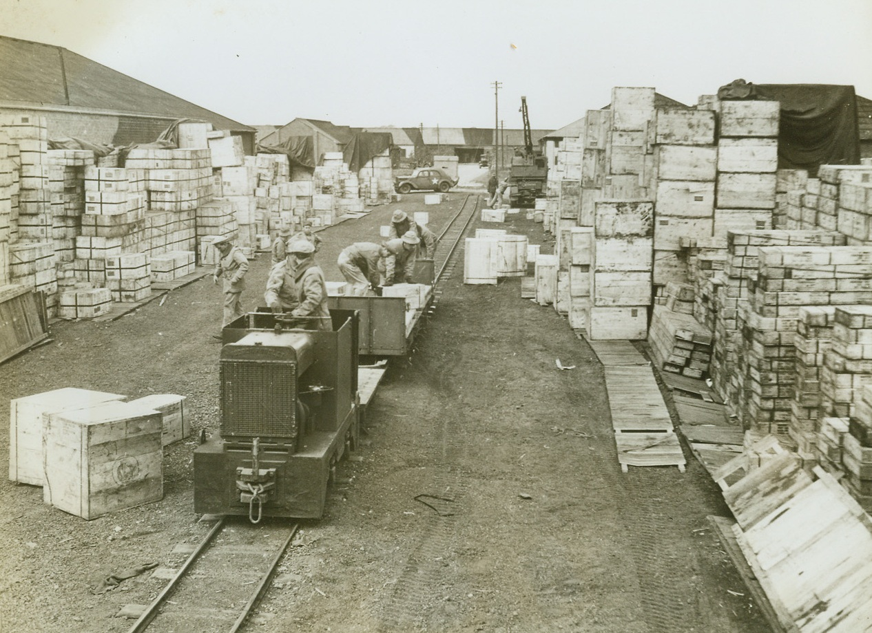 American Railroad in England, 5/22/1943. Somewhere in England -- American soldiers stack crates of supplies on a car that runs along the only U.S.-built and operated railroad in England. Covering 17 miles of trackage, the railroad was built by the Army to haul supplies from the British unloading point to the warehouses, or from U.S. warehouses to British lines for shipment. Credit: ACME;