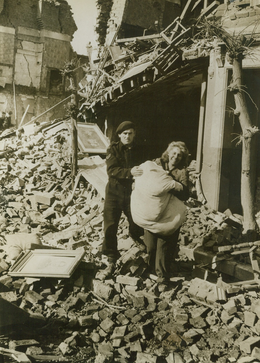 """Smilin' Thru, 5/23/1943.  London, England - Smiling cheerfully as she salvages her belongings from a bomb-wrecked home, this woman is typical of the average Briton. Not even nuisance raids by enemy bombers can shake British confidence in eventual Allied victory. With all Africa conquered and Nazi Europe trembling before the threat of Allied invasion, she knows that it's only a matter of time 'till the Axis surrenders - unconditionally. The German Air Force flew over England again, tonight (May 23), in more that a """"nuisance"""" raid. Bombing and strafing two coastal resort towns, Nazi bombers carried out one of the worst raids since the Battle of Britain. Credit: ACME;"""