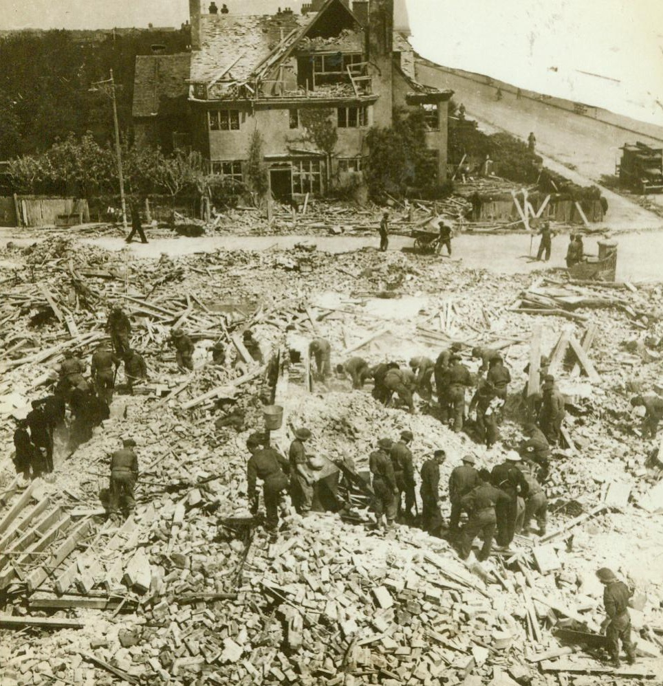 """Another Nazi """"Military"""" Target, 5/21/1943. England -- British soldiers dig in the wreckage of the Auxiliary Territorial Service Building where at least twelve girls of the organization met death when a Focke-Wulf Fighter-Bomber scored a direct hit on the hostel. Fifteen enemy planes took part in the raid on the East England coast town, bombing and machine-gunning the streets from rooftop level. There was also extensive damage done to houses. Credit: ACME;"""