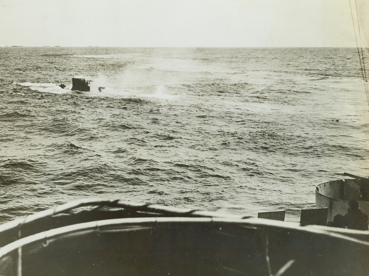 Coast Guard Cutter Sinks Submarine, 5/31/1943. A German submarine attempted to sneak in between a convoy of ships crossing the North Atlantic. Coast Guard Cutters escorting the Merchantmen sighted the U-Boat and The Spencer went into action, aided by The Duane. The Spencer let go a depth charge which brought the sub to the surface; and, then as water rushed into her crushed hull she sank as the Coast Guard picked up her survivors. Bearing down on the sub, The Spencer gets a good look at the sinking sub as she settles in the water. Note the Nazi standing on the deck to the right of the conning tower, and at the right, The Spencer's gun trained on the U-Boat. A swimming German is barely discernable in the water on the right. Credit: U.S. Coast Guard photo from ACME;