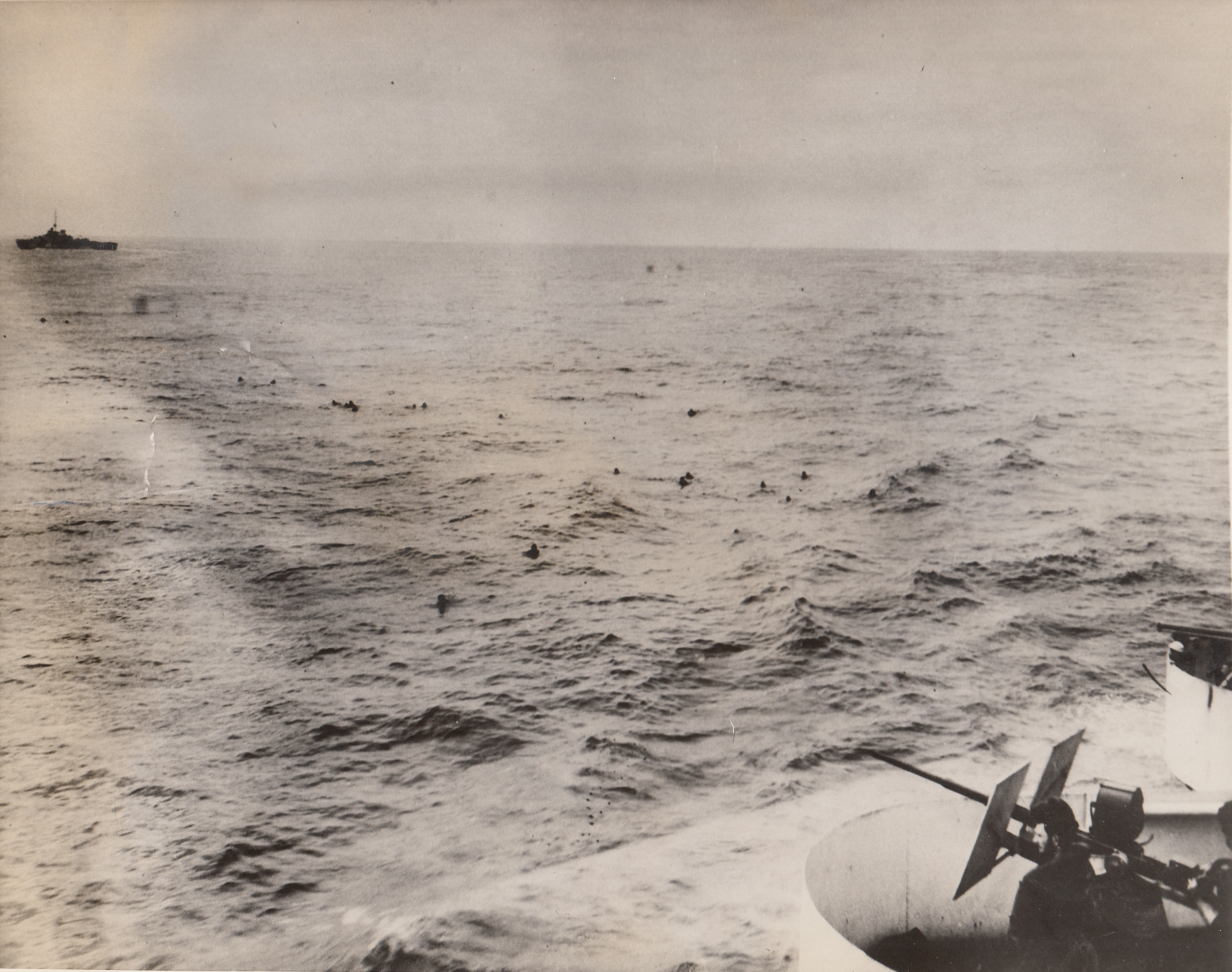 """Subless Supermen, 5/31/1943. North Atlantic – """"Oh where, oh where has that submarine gone"""" is the song of these Nazis as they paddle for their lives toward the U.S. Coast Guard cutter Spencer, which forced up and sank their undersea craft in a recent North Atlantic action. The U.S. Coast Guard Cutter Duane, which aided in the rescue, is shown in the background. The enemy sub was trying to sneak into the midst of a big convoy when the Spencer (right foreground) sent it to Davy Jones.;"""