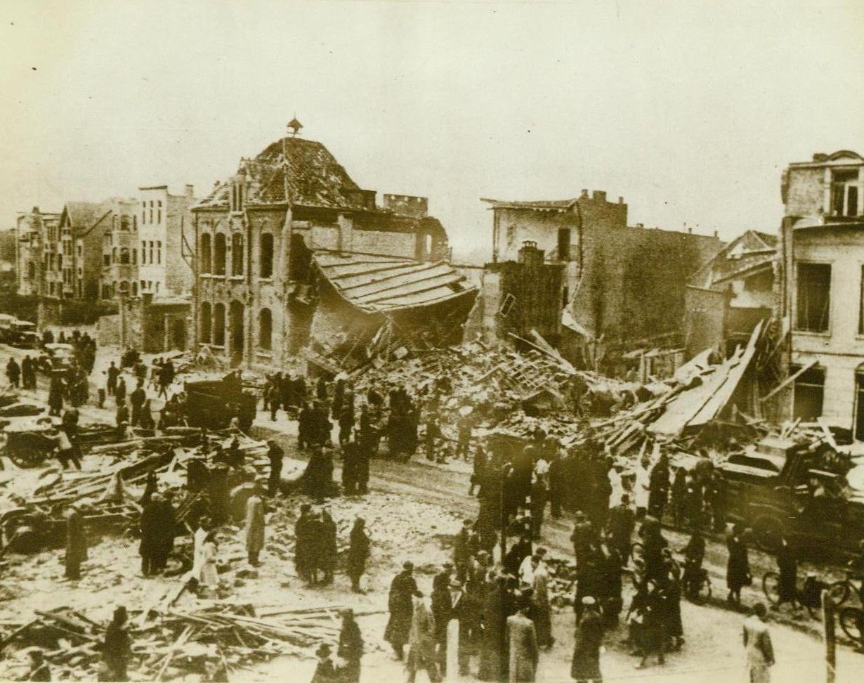 """After Our Bombers Left, 5/20/1943. Antwerp—Rushing from their shelters as the """"all clear"""" sounds, civilians throng in the streets of Antwerp to survey the damage done by American bombers in their devastating daylight raid. Photo was recently received in England through a neutral source. 3/20/43 (ACME;"""