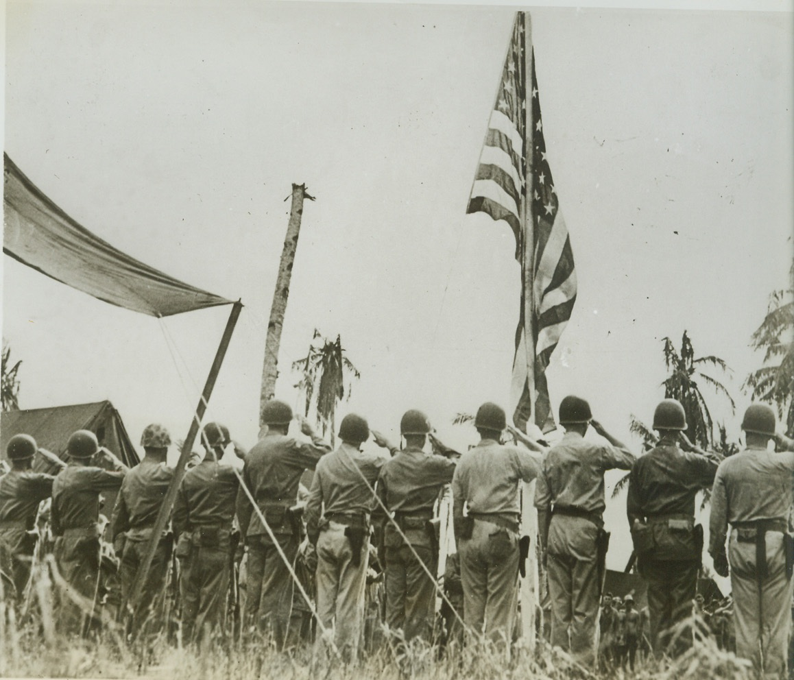 The Call to Colors, 8/6/1944. Guam – Still attired in their battle helmets, Marines of the First Provisional Marine Brigade snap to a smart salute as the American flag waves aloft in the first flag-raising ceremony in front of Maj. Gen. Roy S. Geiger's headquarters at Agat, Orote Peninsula. Credit (ACME);