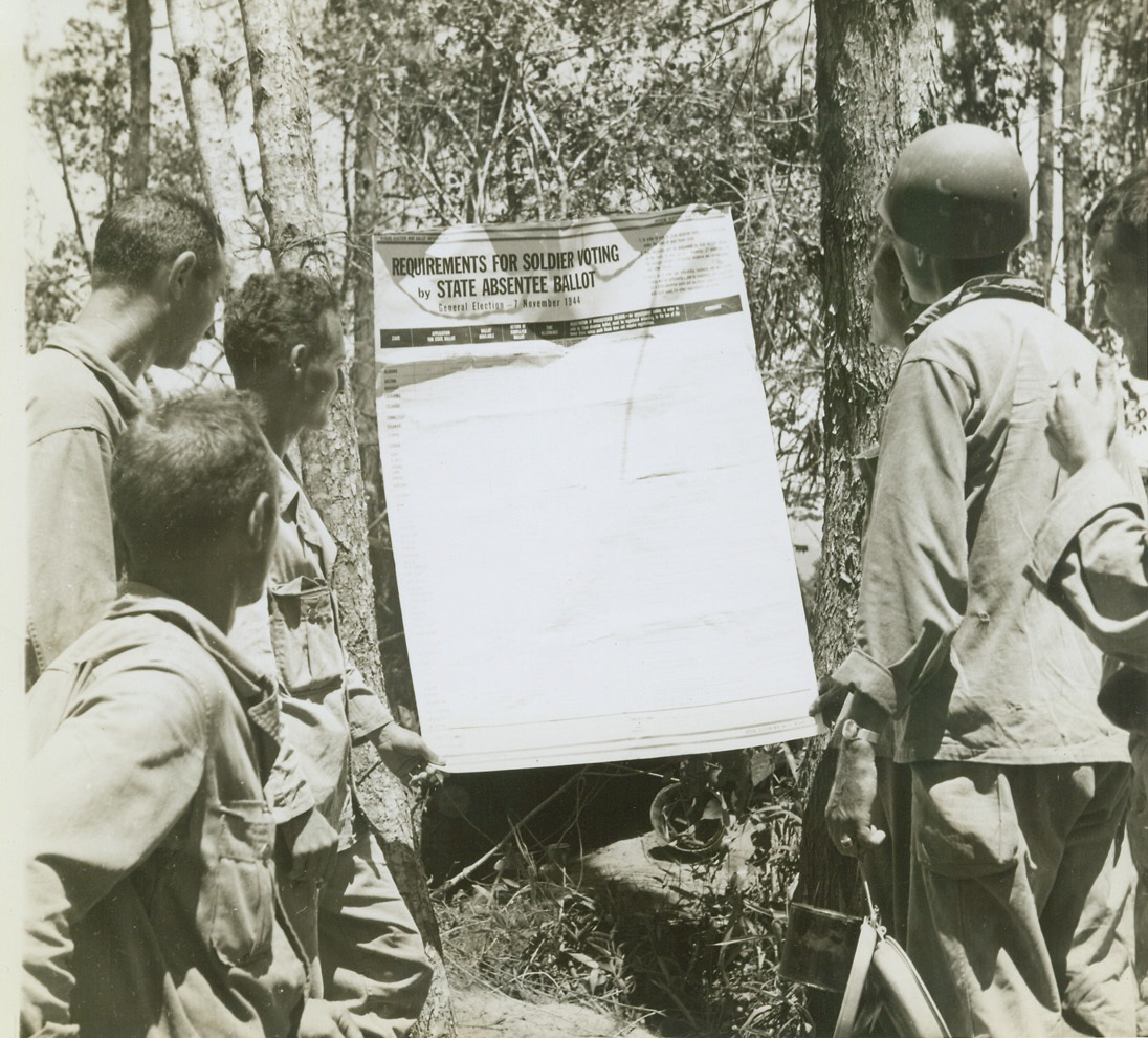 YANKS IN NEW GUINEA SEE ELECTION BALLOT, 8/11/1944. NEW GUINEA – Near the battle front down the Driniumor River, 16 miles east of Aitape on New Guinea, American soldiers take time out from war duties to read requirements for soldiers voting by state absentee ballot. Credit: OWI Radiophoto by Tom Shafer for ACME;