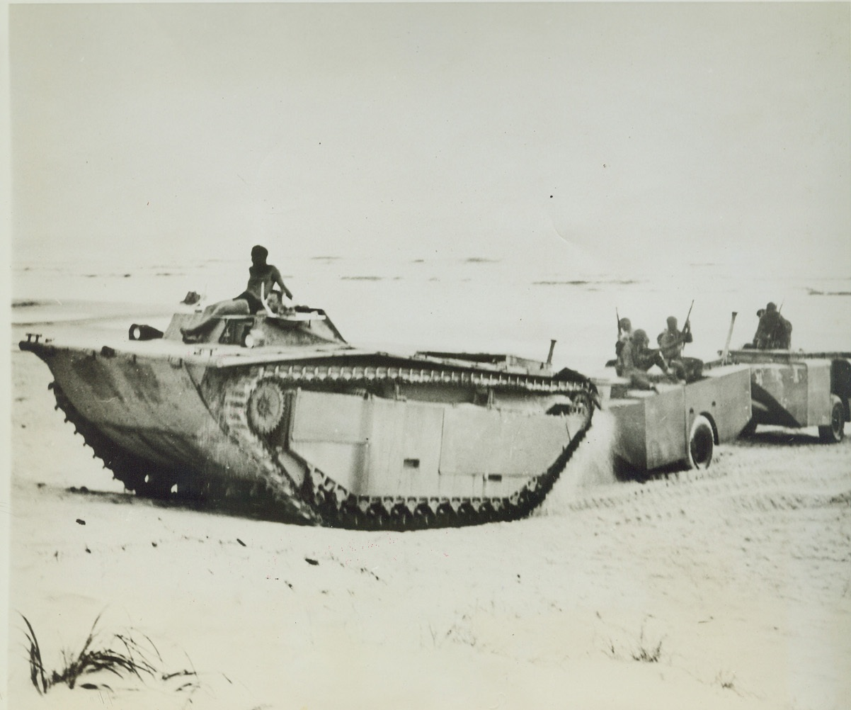 AMPHIBIOUS SUPPLY TRAILERS, 8/13/1944. CAMP LEJEUNE, N.C. – An amphibious tractor hauls ashore a new amphibious cargo trailer during a series of test by US Marines. The water-tight trailers have a capacity of 220 cubic feet. When used in combat, they will insure the delivery of supplies in a more usable condition. Credit: U.S. Marine Corps photo via OWI Radiophoto from ACME;