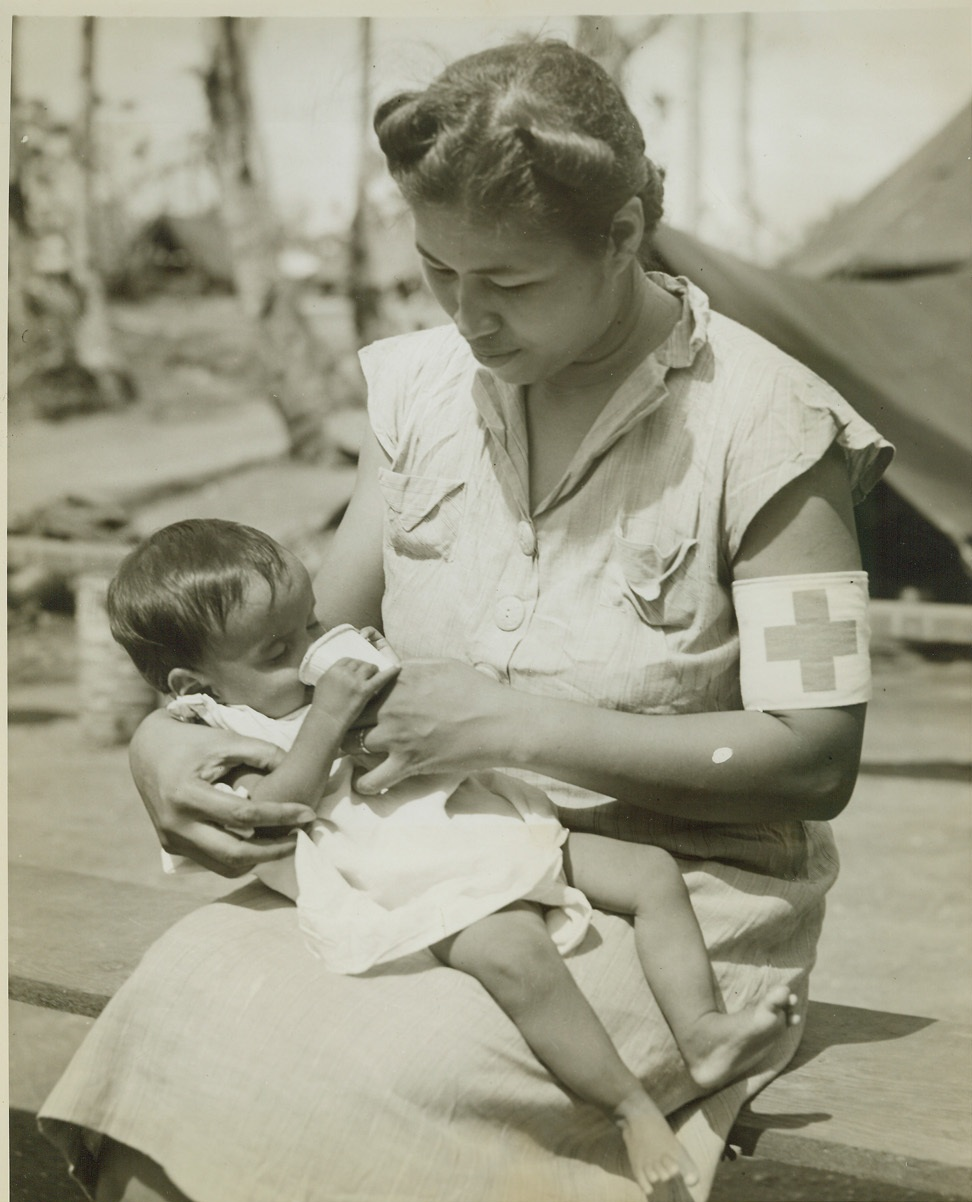 FIRST MILK FOR GUAM CHILD, 8/23/1944. GUAM – Nurse Maria S. Aguon gives this little 9-months-old baby its first taste of milk since birth at the civilian internment camp near Agana on the island of Guam. Many Chamorro mothers now in the camp, were fed so poorly under Japanese domination, that they had no breast milk for their babies. Credit: OWI Radiophoto by Stanley Troutman for ACME;