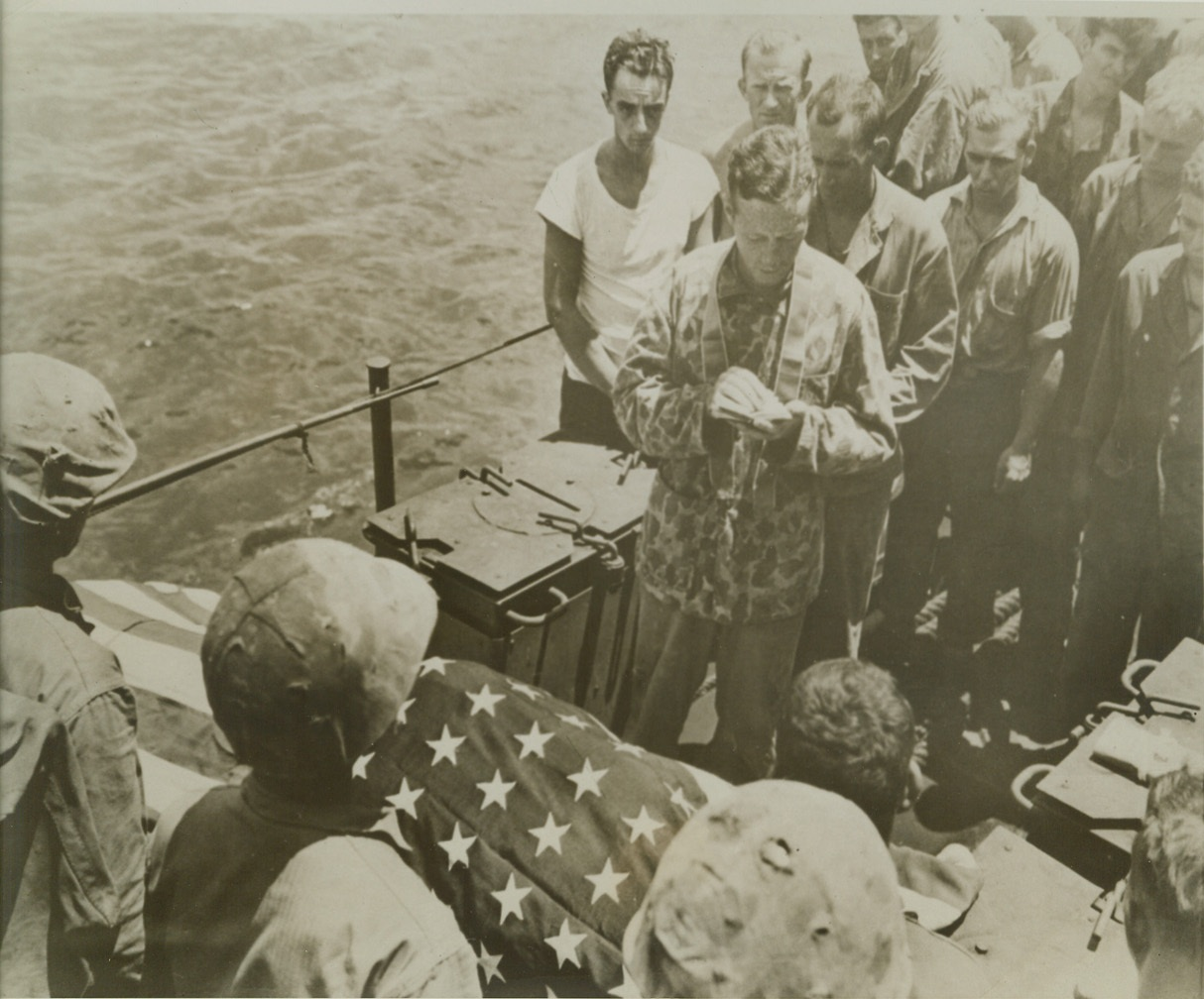 LAST RITES FOR MARINE, 8/8/1944. SOMEWHERE IN THE PACIFIC – Still wearing his camouflaged tunic, Lt. (JG) Joseph P. F. Gallagher, USNR, Catholic Chaplain, 840 Grand Concourse, Bronx, N.Y., reads the burial service for a Marine who died in the assault on Tinian Island. His friends form an Honor Guard for the burial at sea. Credit: U.S. Marine Corp photo via OWI Radiophoto from ACME;