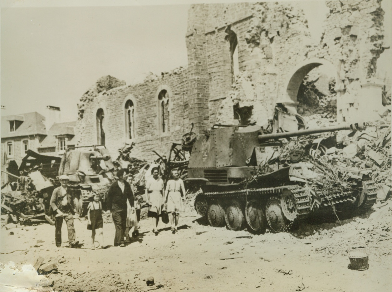 UNWELCOME GUEST IN RONCEY, 8/11/1944. RONCEY, FRANCE – These citizens of Roncey, returning to their home town after the wave of battle had swept past it, are greeted by wreckage and debris-strewn streets. German tanks and other pieces of wrecked or abandoned enemy equipment litter the roads. Credit: ACME;