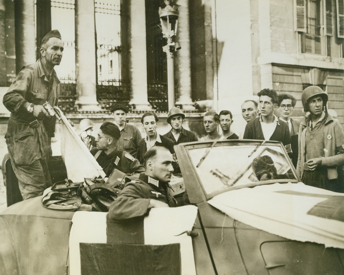 NAZIS SURRENDER CHAMBER OF DEPUTIES IN PARIS, 8/30/1944. FRANCE—Two Nazi officers who were part of the 400 Germans who barricaded themselves in the Chamber of Deputies in Paris and fought off liberating troops, wait to be driven away after their surrender to French partisan forces. The flag of truce is in the back of the car.Credit: Acme;