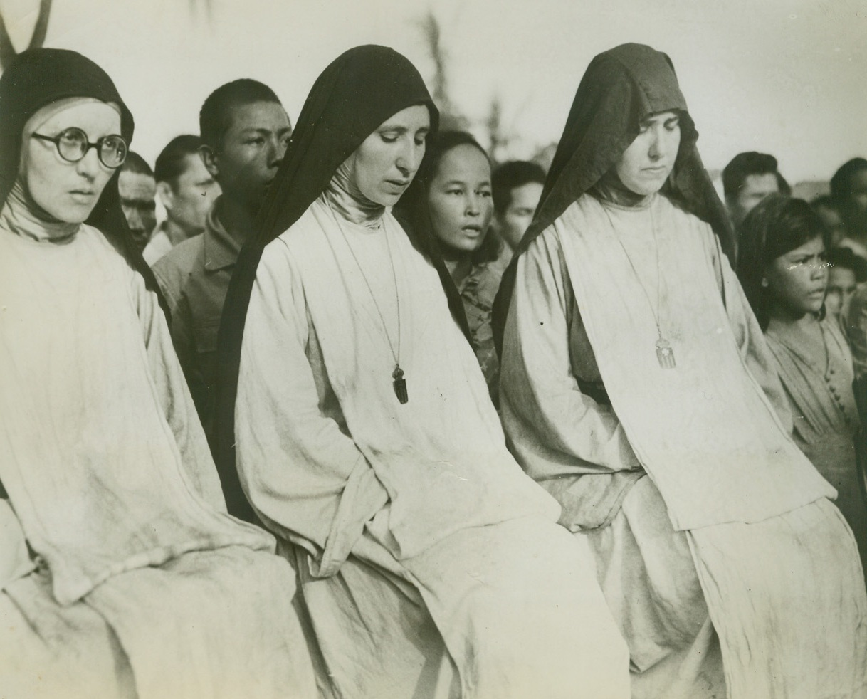 """NUNS ATTEND FIRST MASS ON LIBERATED SAIPAN, 8/1/1944. SAIPAN ISLAND—Catholic nuns attend the first Mass held on Saipan since 1940, when the Japanese abolished Christian rites. Attending Mass with them are other civilians freed from the Japs by the capture of Saipan by the U.S. """"triphibian"""" (air-land-sea) forces.Credit: Official U.S. Navy photo from Acme;"""