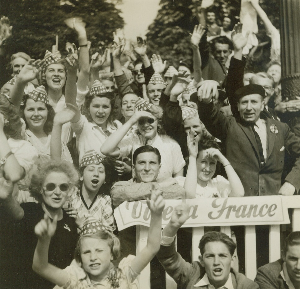 VIVE THE STARS AND STRIPES, 8/31/1944. PARIS—Wild with joy over the liberation of Paris, and singing the praises of their American allies, these celebrating Parisians let the Stars and Stripes go to their heads. Wearing the gay paper hats, they cheer and wave as the forces of liberation march past on parade. Credit: Acme photo by Bert Brandt for the War Picture Pool;