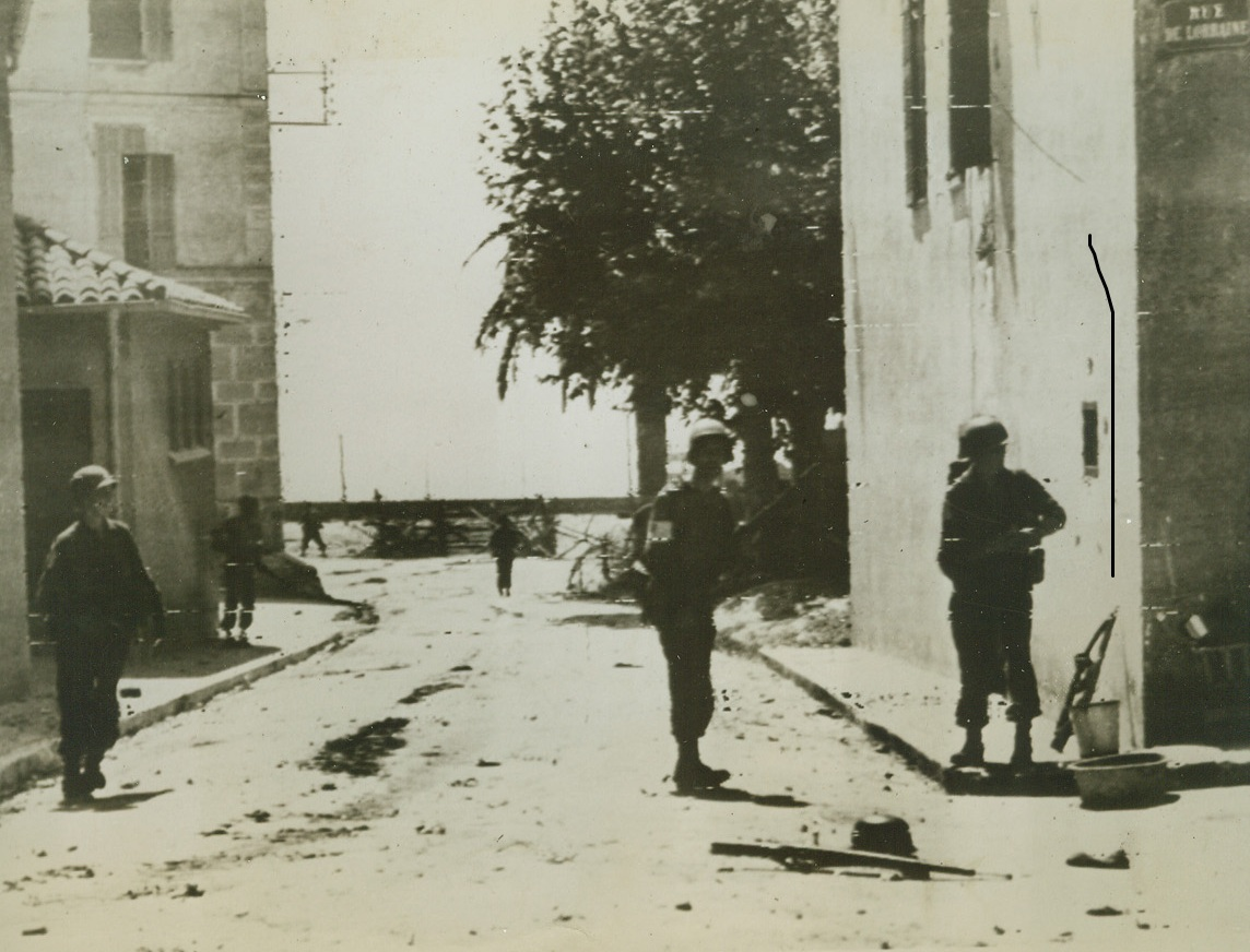 Expanding New Beachhead, 8/16/1944. Moving cautiously and watching every house for enemy snipers, American Infantrymen advance through a street in a town east of Toulon. In the background, can be seen the beach, one of the many points Allied invasion forces hit along the coast of Southern France. Note German rifle and helmet (right, foreground). Credit: ACME PHOTO BY SHERMAN MONTROSE FOR WAR PICTURE POOL VIA ARMY RADIOTELEPHOTO.;