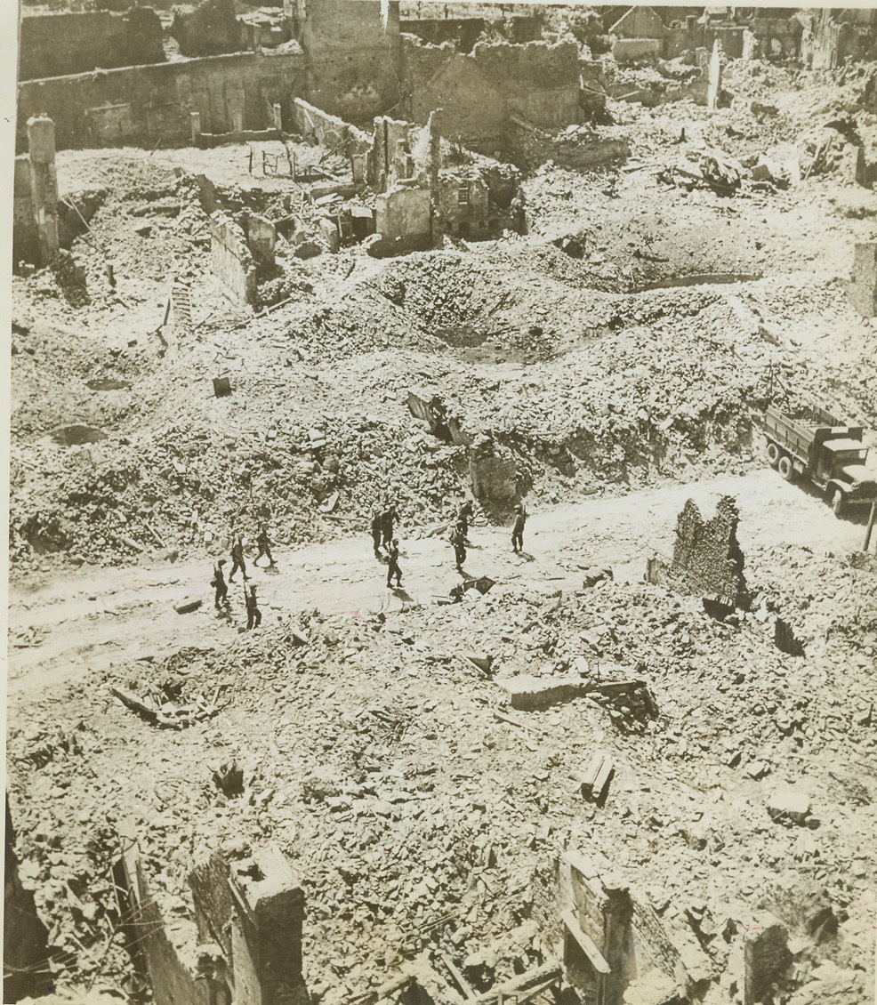 Bomb-Torn St. Lo Plays Host to Yanks, 8/12/1944. ST. LO, FRANCE -- It was a victory in ground gain only for American troops which took St. Lo. Practically all of the city was in the same condition as the section shown here. Soldiers amble down the street looking to both sides, where, stretching as far as the eye can see, is rubble and debris from shattered buildings and emplacements. Credit (ACME) (WP);