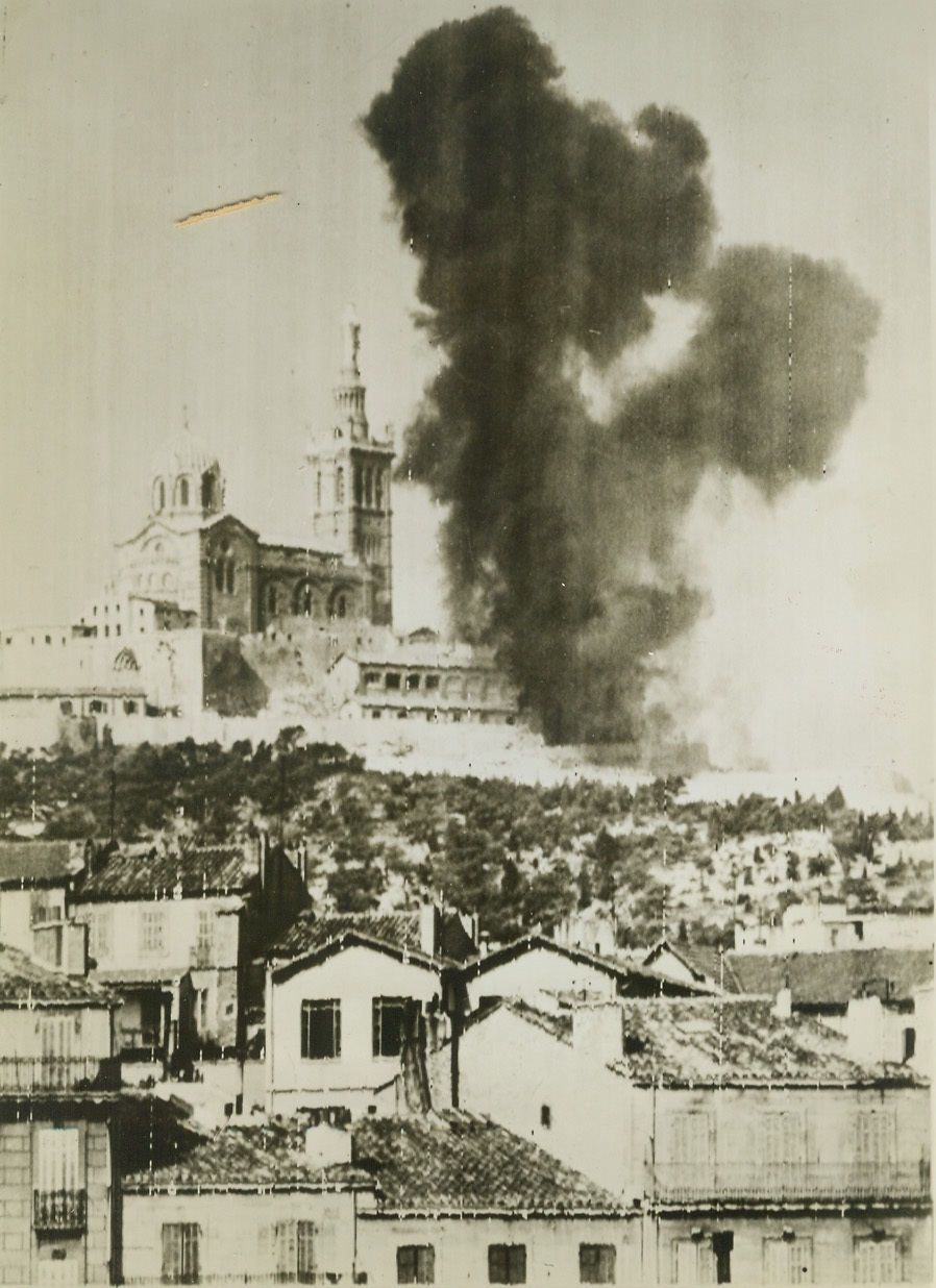 Cathedral An Enemy Target, 8/31/1944. FRANCE -- Smoke rises from a hit near the famous Cathedral of Notre Dame De La Garde situated on a hill in Marseille and the target for German fire after the city was captured by French forces. Credit (Army Radiotelephoto From ACME);