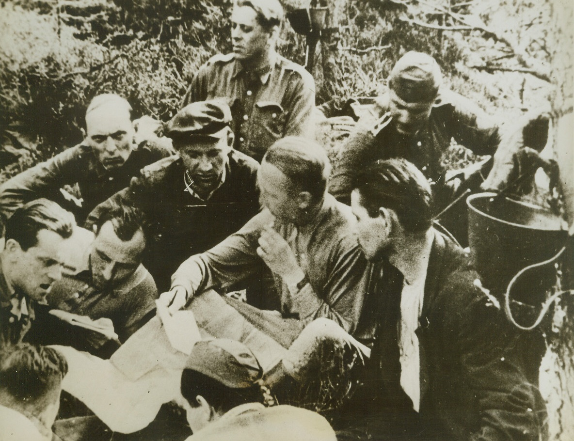 THEY FIGHT TO FREE POLAND, 8/23/1944. POLAND—Guerillas of the Polish Home Army, some wearing uniforms taken from ambushed German soldiers, plan an expedition with their commanding officer. Members of Poland's 9th Infantry Regiment, the partisans operate behind the German lines. Credit: Acme;