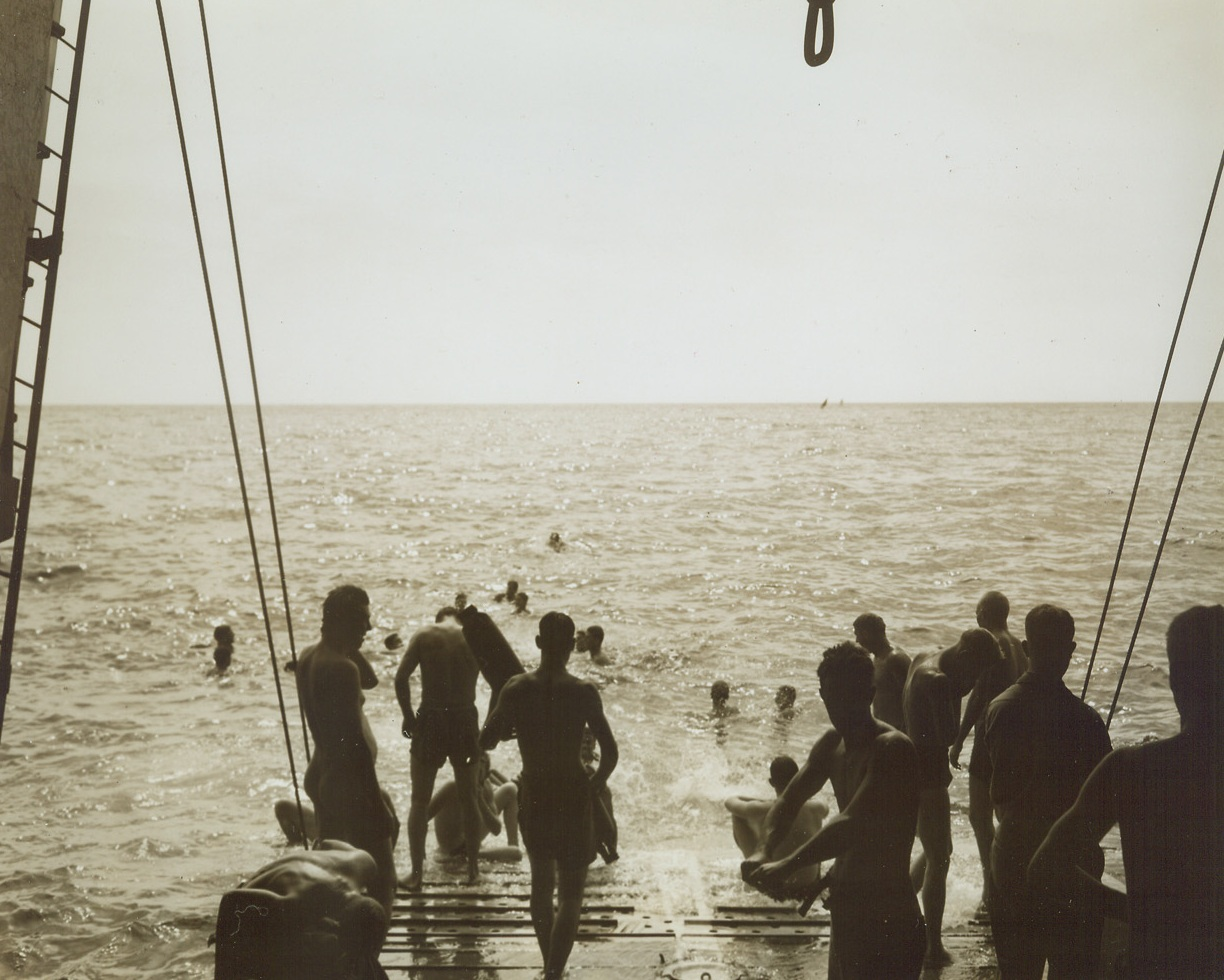 NO TIME FOR NERVOUSNESS, 8/22/1944. AT SEA—Veterans of the Italian and Sicilian campaigns and old timers at the business of invasion, infantrymen of the 45th Division relax before heading into the invasion of southern France. There's no time for invasion jitters when the blue Mediterranean invites a fighter to take a swim. The boys dive off the [illegible] will soon bring them to the French coast. Credit: Acme photo by Sherman Montrose for the War Picture Pool;