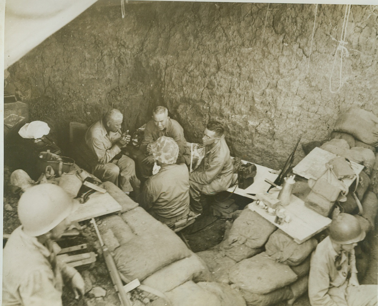 Underground Guam Command Post, 8/22/1944. GUAM -- In this super foxhole turned into a command post on Guam, Maj. Gen. Roy S. Geiger (left), commander of Third Marine Amphibious Corps, confers with Maj. Gen. Allen H. Turnage, USMC. Sand bags and alert sentries furnish additional protection against possible Jap interruption of this battlefront strategy huddle.  Credit (Marine Corps Photo from ACME);