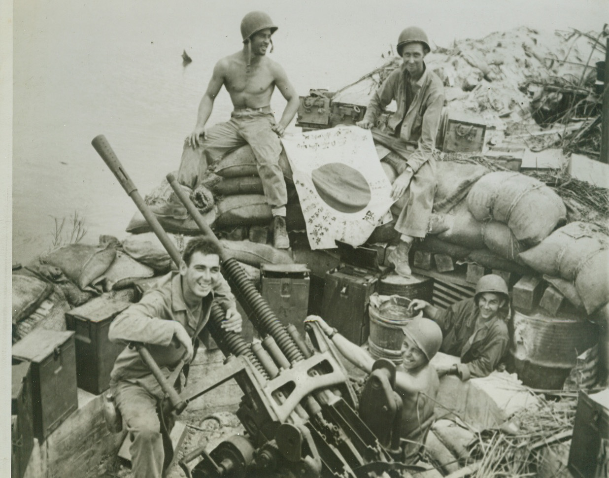 Jap Gun on Guam a Yank Prize, 8/2/1944. GUAM -- Useless now except as a memento of action gone by is this captured Jap gun taken during the American assault of Piti, Jap Naval station at Guam. In the gun pit are Sgt. Joe A. Grimes, Groesbeck, Tex. (rear, left) and Cpl. James W. Redding, (rear, right), Atlanta, Ga., examining a Jap flag, while (left to right, front) Pfc. Joe Woolsey, Jerseyville, Ill.; Pfc. Warren Jordan, Newark, N.J.; and Pfc. Joe Gilles, LaCrosse Wis., exhibit the gun. Credit- WP-(ACME);
