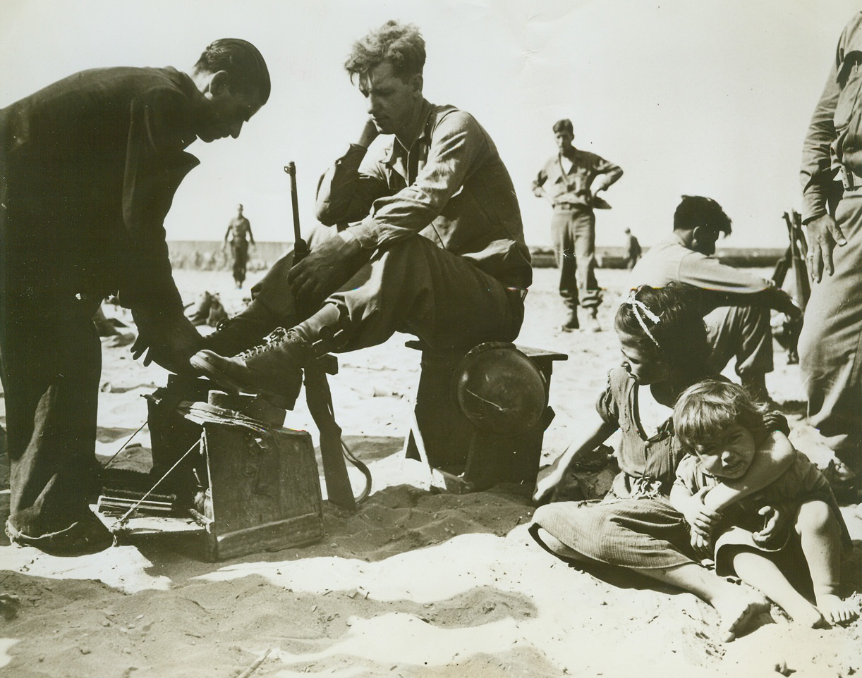 """Polishing Up for Invasion of """"Fashion Center"""", 8/19/1944. ITALY – All set for style-conscious France is Pfc. James P. Royle, Boston, Mass., getting a last minute shoeshine before shoving off from an Italian port for the invasion of Southern France. Credit (Signal Corps Photo from ACME);"""