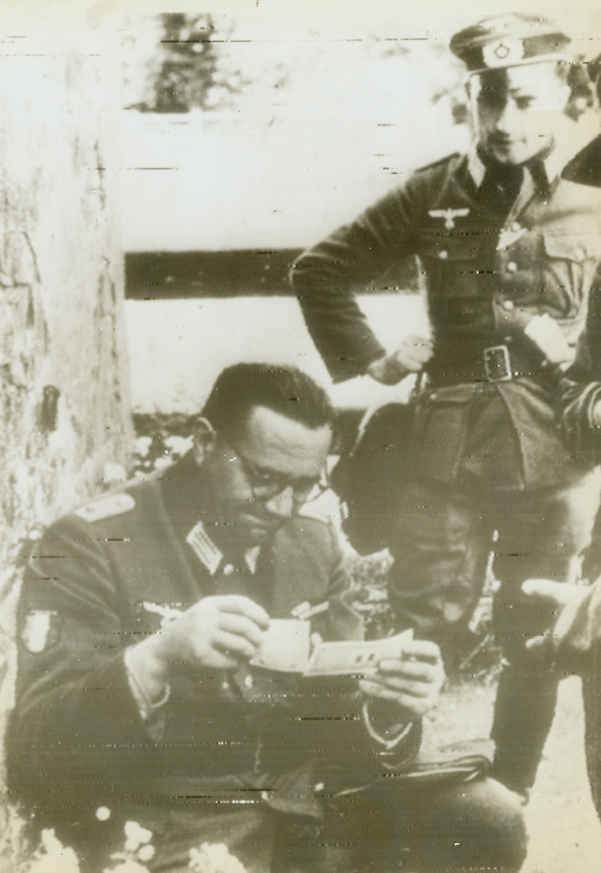 """""""Roosevelt's Fake Money"""", 8/4/1944. According to the German caption accompanying this photo, radioed today from Stockholm, Jacques Doriot, French Nazi leader attired in German uniform, examines invasion francs, dubbed by the German caption """"Roosevelt's fake money.""""Credit (ACME Radiophoto);"""
